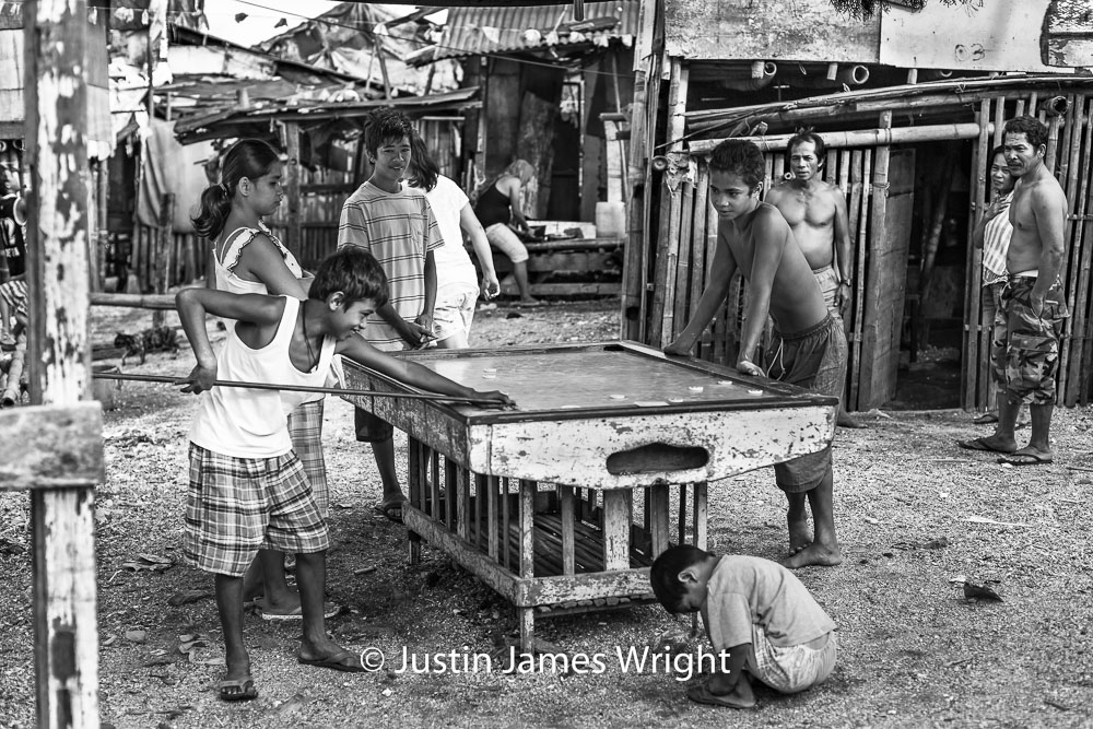 Recreation . - An occasional game of  pitsa  (Filipino billiards with discs), well-deserved reward at the end of a day's work.  Resilience - The Isla Pulo Community, Philippines.  February 2013. Canon EOS Mk III, EF 50 mm, F 2.8, 1/500 sec.