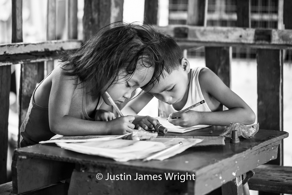 Meeting of the Minds   Marc and Danielle May, both six, put their pencils and minds to good use, as they work on the day's school assignments.  Resilience - The Isla Pulo Community, Philippines.  July 2013. Canon EOS Mk III, EF 100 mm, F 2.8, 1/160 sec.
