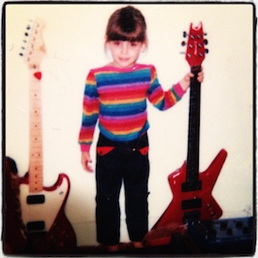 Shanti as child, just barely taller than the guitars