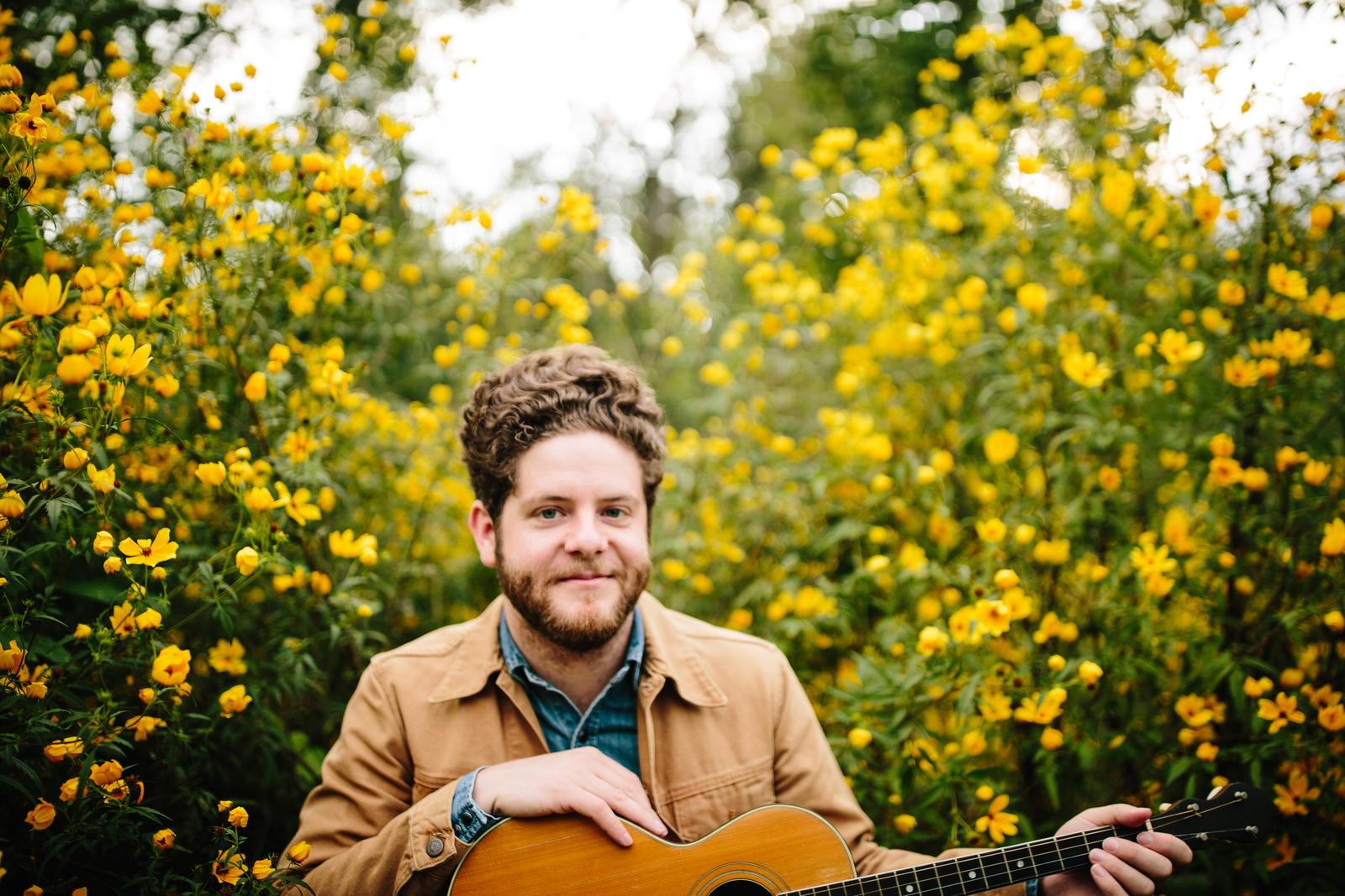 Josh Lovelace in field with guitar