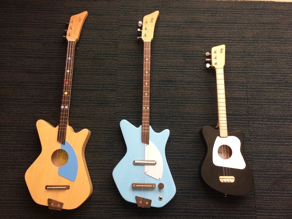 Three Loog guitars (from left to right): Original Loog II Acoustic, Electric in blue, Mini in black