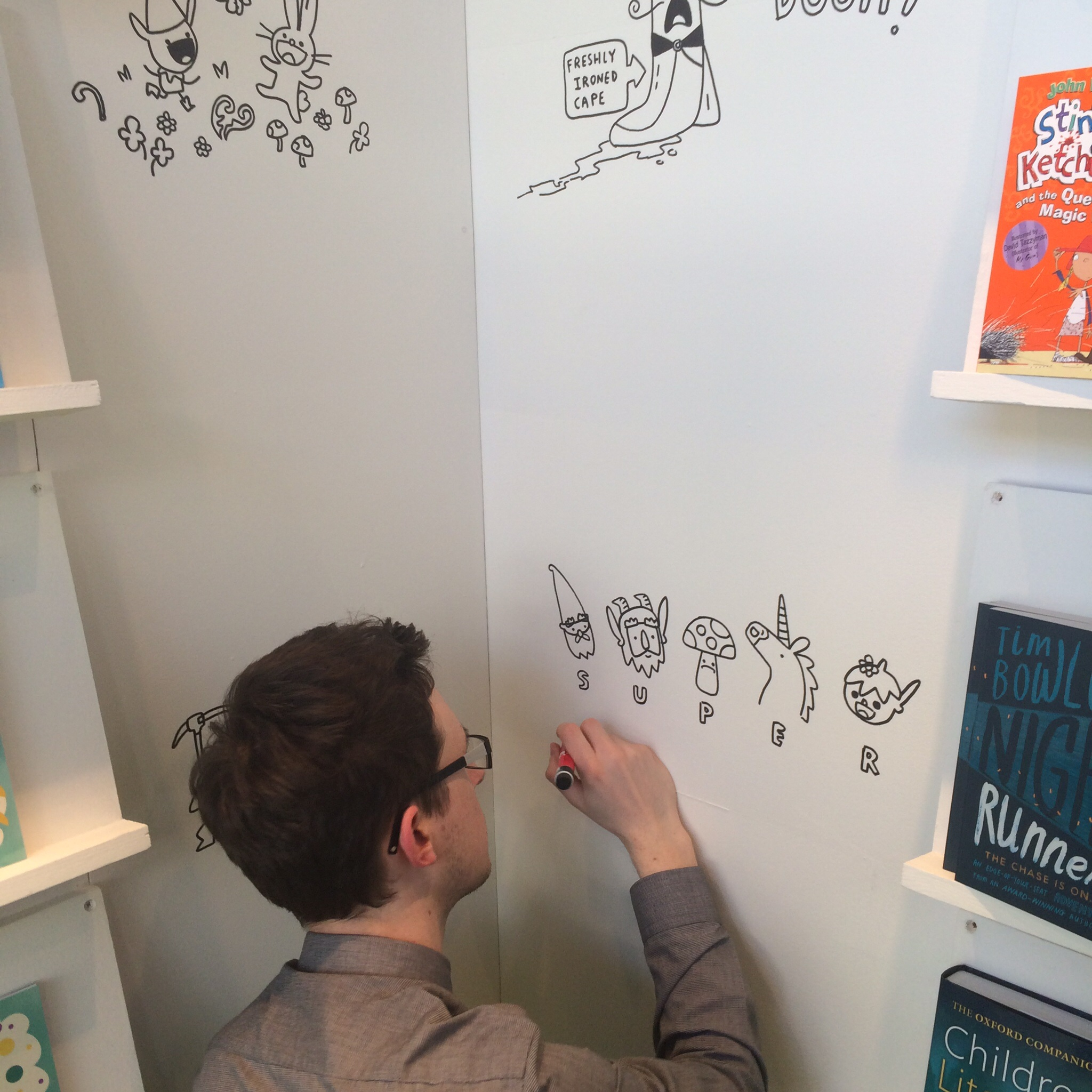 Matty Long  drawing characters from his 'Super Happy Magic Forest' on OUP's walls.