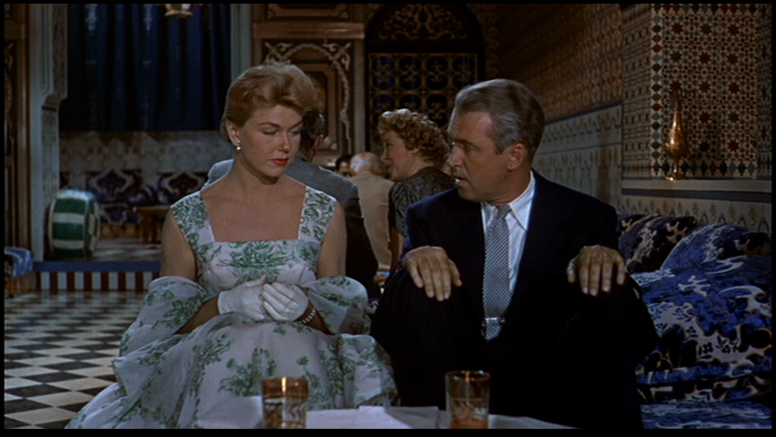 Doris Day sitting next to Jimmy Stewart who doesn't know where to put his legs in the Marrakesh restaurant scene in the 1956 The Man Who Knew Too Much.