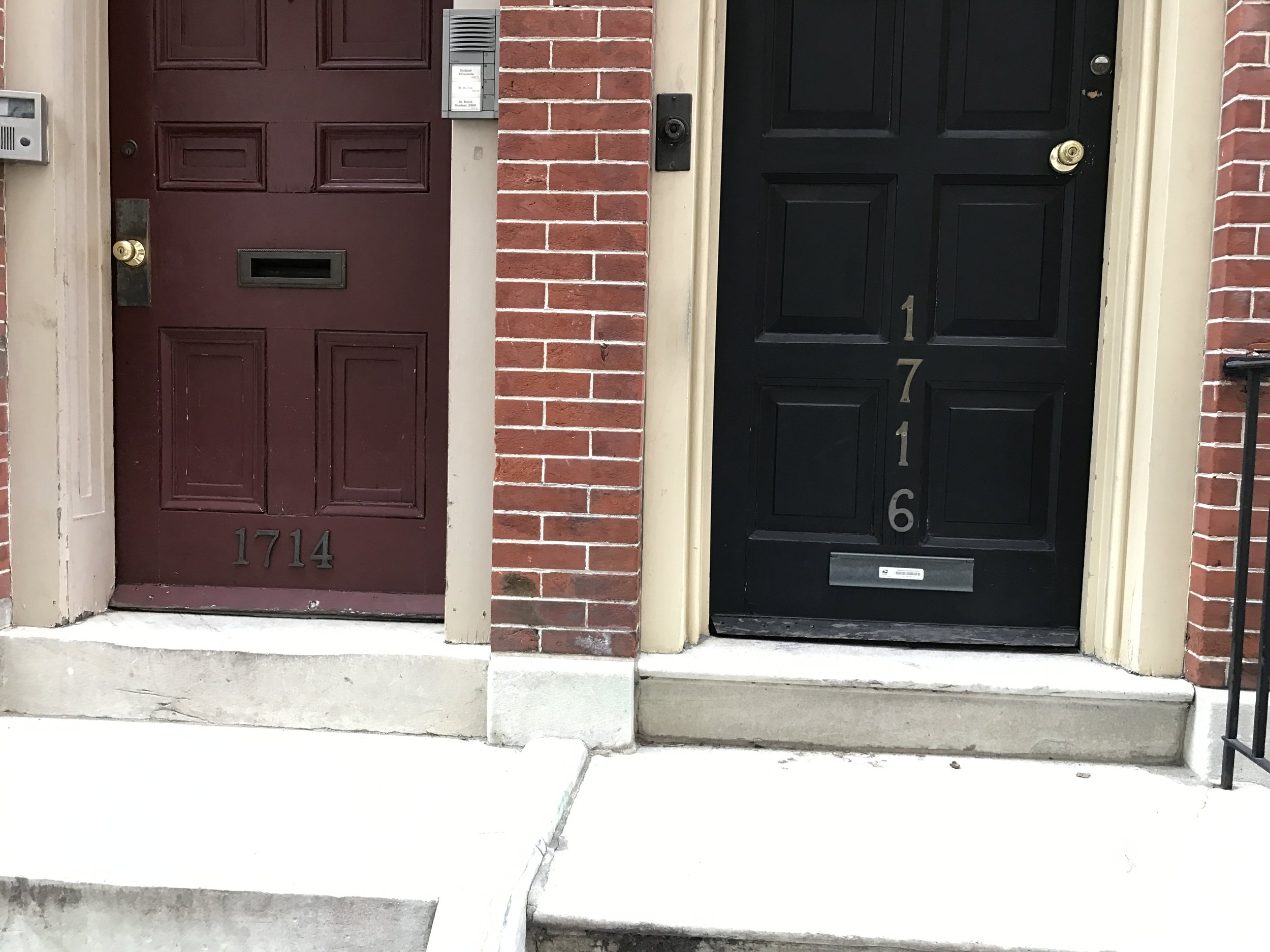 Two doors with their numbered street addresses in plain view