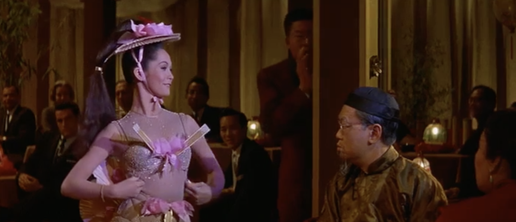 Nancy Kwan as Linda Low revealing a little too much of herself for Master Wang (Benson Fong)