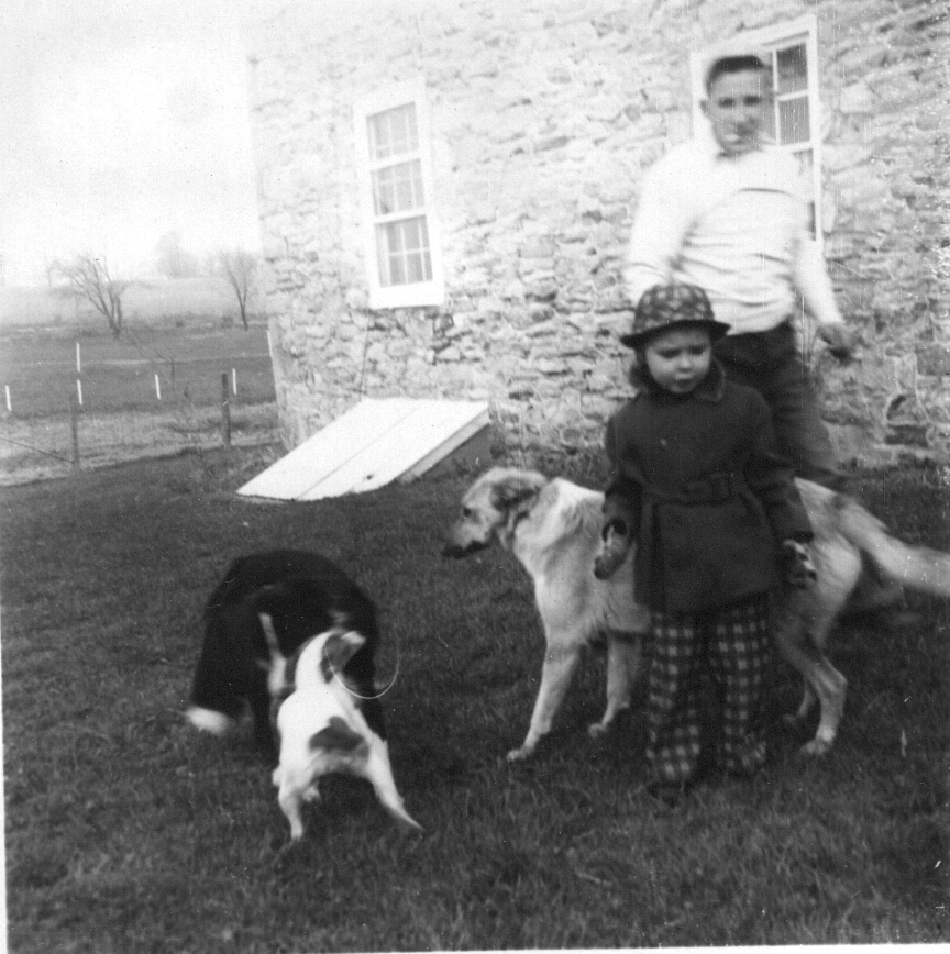 That's my father and I with King, I think, behind me in a photo dated November 1953 so I would have been four. The black dog looks like it might be Shep, and the little dog is probably Debbie, my aunt and uncle Jane and Allen's dog. You can see the Great Stone House in the background.