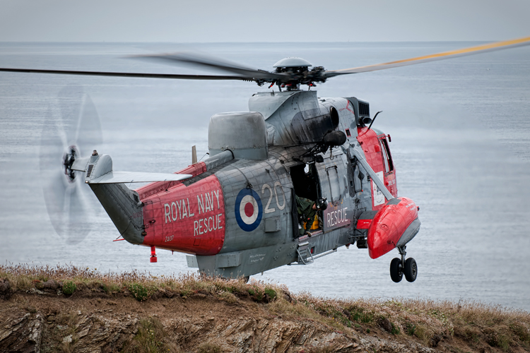 'Maisy' guides the crew down from the back as he hangs out of the door of the Sea king Mk5 during a pinnacle landing.