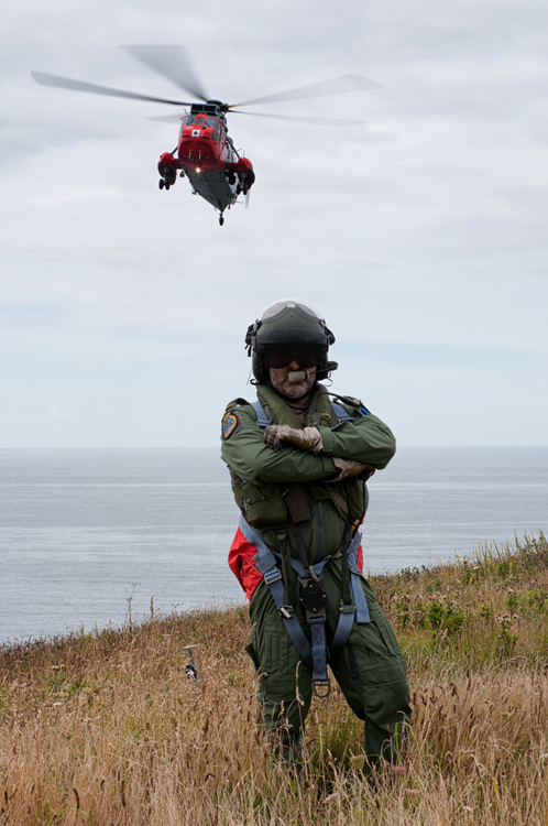 The hero shot as 'Grossy' poses for the camera with a 771 NAS Sea King Mk5 hovering behind.