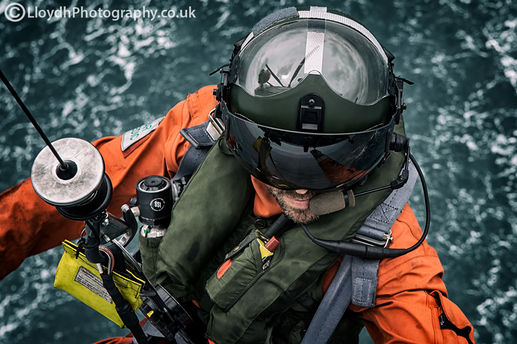 771 NAS Aircrewman reaches out for the grab handle as the winch operator brings him back up to the aircraft.