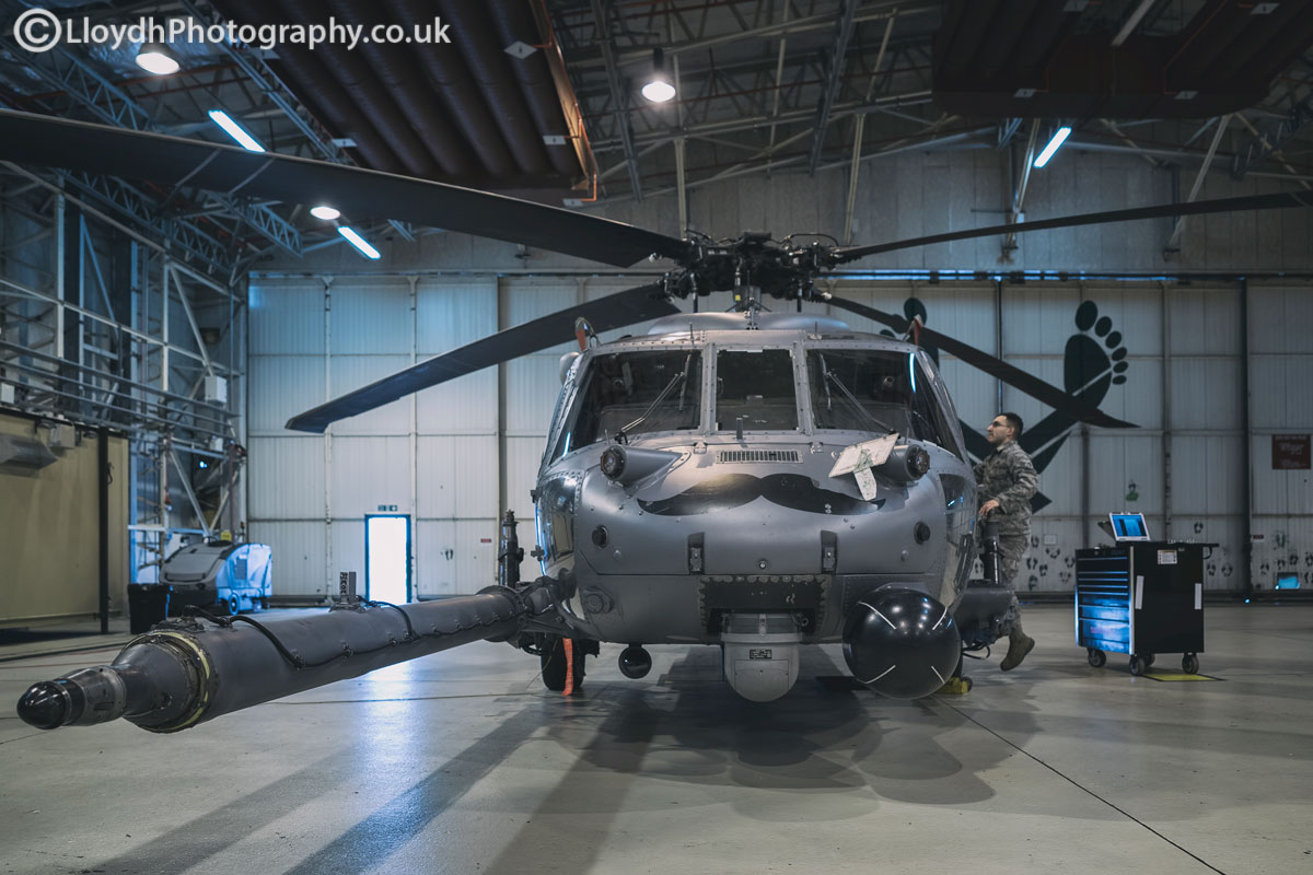 HH-60G Pave Hawk undergoing maintenance work, the iconic green feet printed on the hangar doors.
