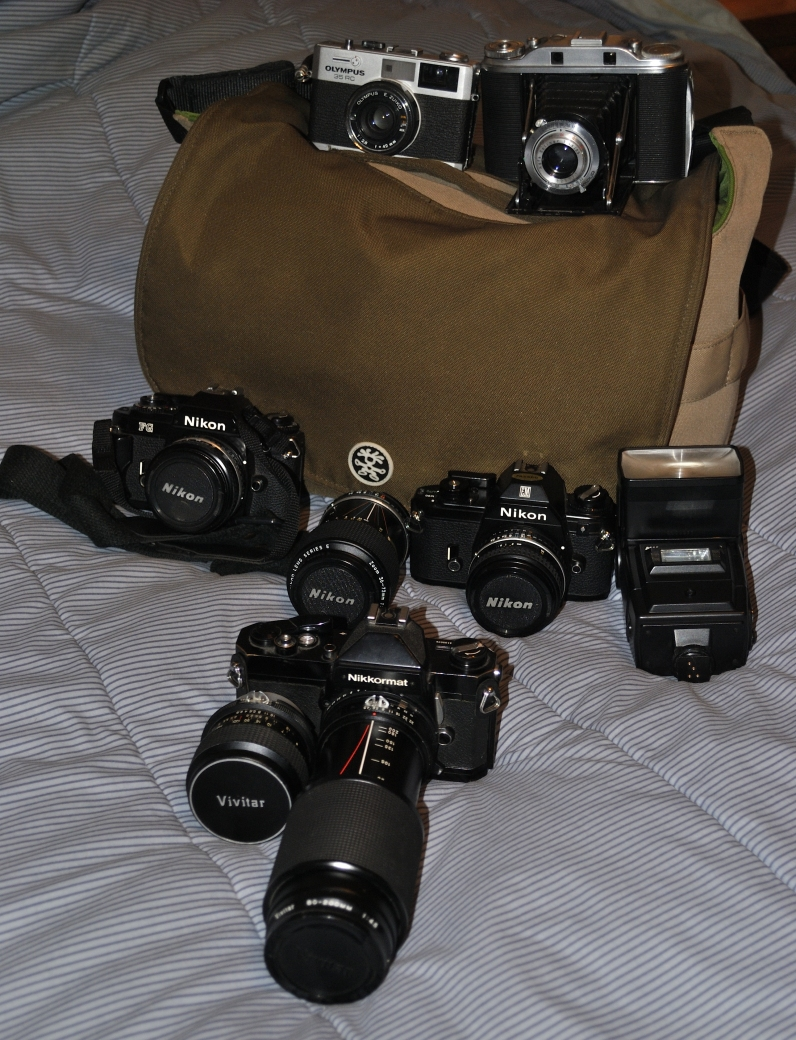 On top of the bag (L to R): Olympus 35RC. Ansco 120 'folder'.  In front of the bag (L to R): Nikon FG camera, Nikon E 50mm f/1.8 lens.  Nikon 35 to 72mm F/3.5 zoom lens.  Nikon EM camera, Nikon E 28mm f/2.8 lens.  Nikon SB-16 Speedlight.   In front of the Nikon gear:  Nikormat FT3 with Vivitar 35mm lens and 70mm to 210mm f/4.5 zoom lens.