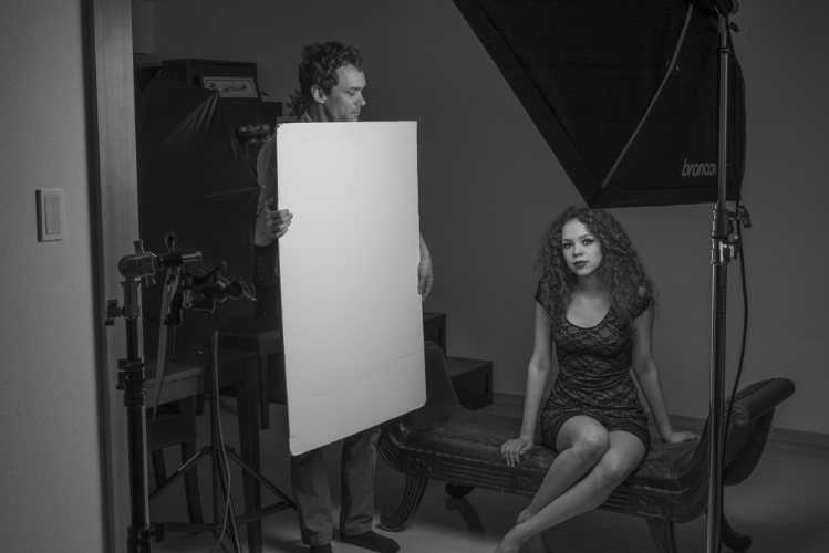 Using a foam core board as a reflector to add fill light. All of the light is coming from the softbox in the right side of the frame. The umbrellais switched off in this image.