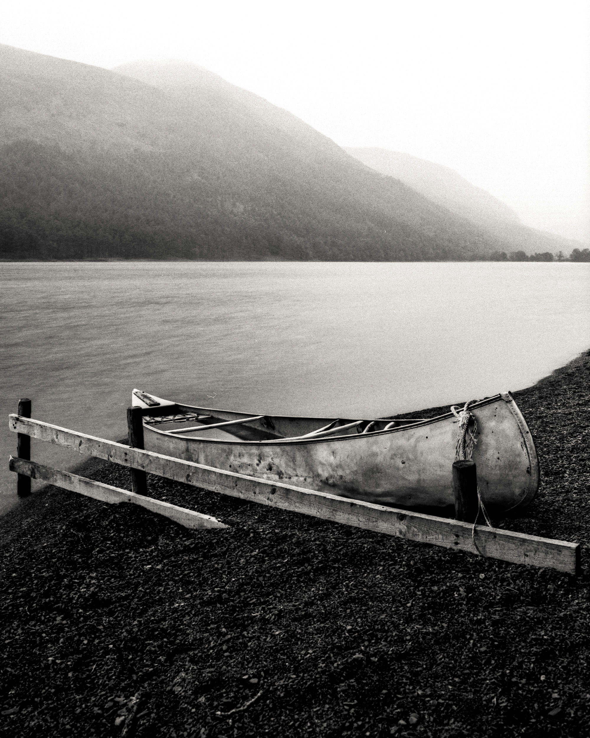 Mamiya 645 Pro TL, 45mm, Delta 100.     Finding a silver boat with a wooden fence next to it on a dark rock beach is just a tone perfect subject for black and white. The boat set against the mountain with a combination of rain and sun in the background for me creates a quite dynamic image with a very static subject.
