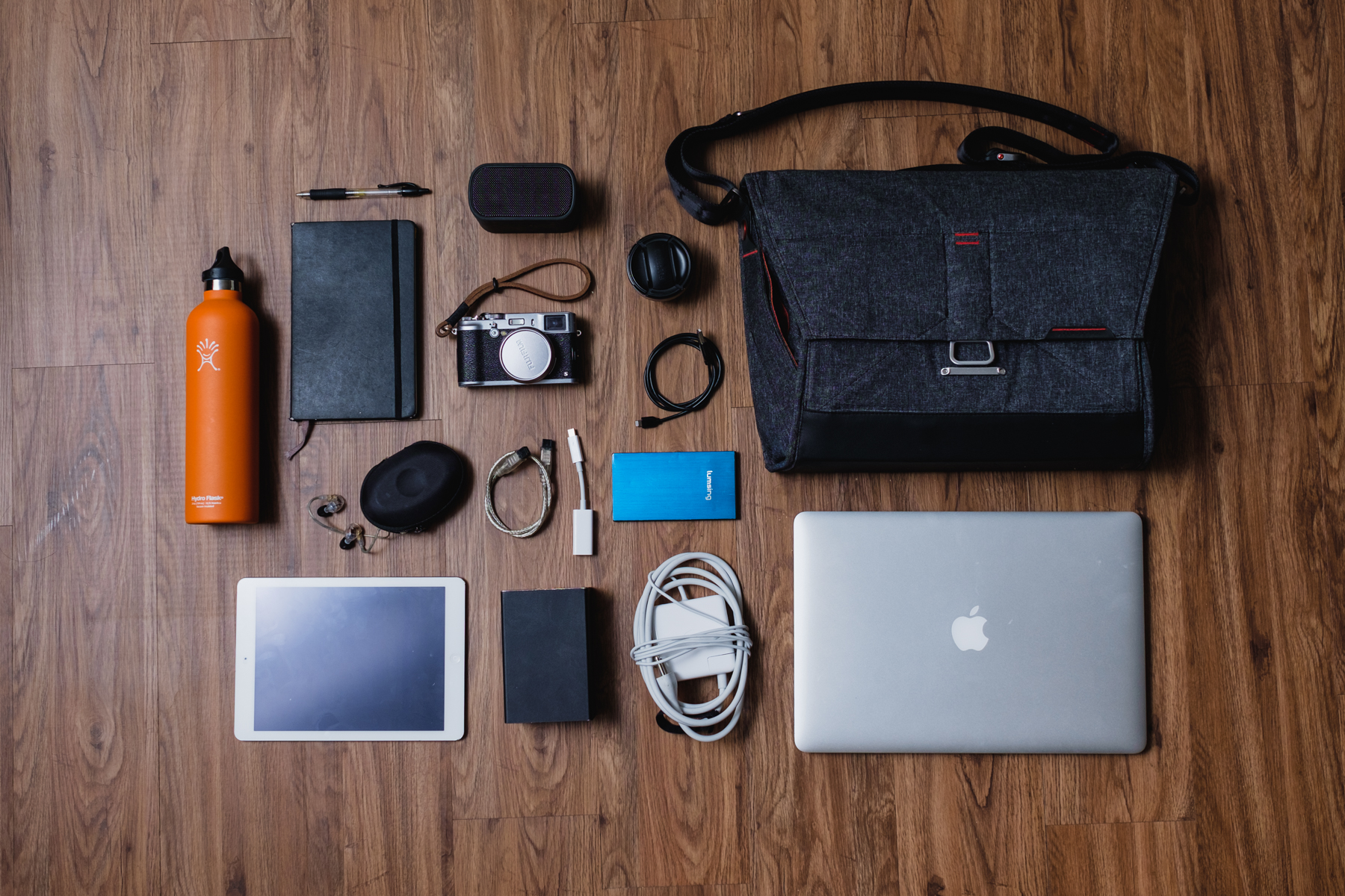 "This is my photo shoot day bag 'if my car was on fire, grab this bag' - Hydro Flask water bottle, Moleskine Notebook, Pilot G-2 Pen, Shure SE535 Earphones, Apple iPad Air, UE Bluetooth Speaker,  Fujifilm X100s , Fujifilm  TCL-X100  Conversion Lens  , Apple Lighting to USB Cable, Cable for the Raid thunderbolt drive, OWC Raid 0 Drive, Portable battery,  Apple Macbook 15 "" & Charger."