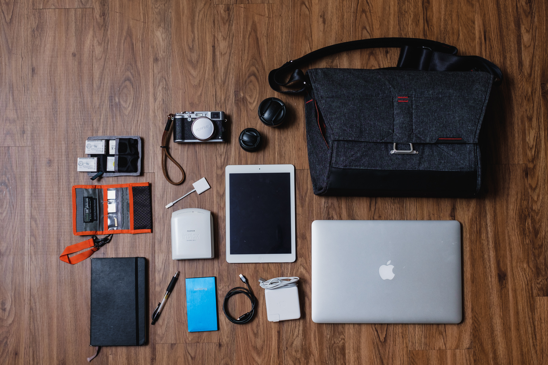 """This is my travel setup 'Lets go somewhere bag' - Think Tank Photo Battery Holder, 4x Fujifilm NP-95 Batteries, Think Tank Photo SD Pixel Pocket Rocket,SD Cards, Moleskine notebook with Pilot G-2 Pen,  Fujifilm X100s  camera, Fujifilm  WCL-X100  &  TCL-X100 Conversion Lenses ,Apple iPad Air, Apple Lighting to SD Card Adapter,    Fujifilm Instax  Printer SP-1   , Portable charger, Apple Lighting to USB Cable,Apple MagSafe Charger, and  Apple Macbook Pro 15"""""""