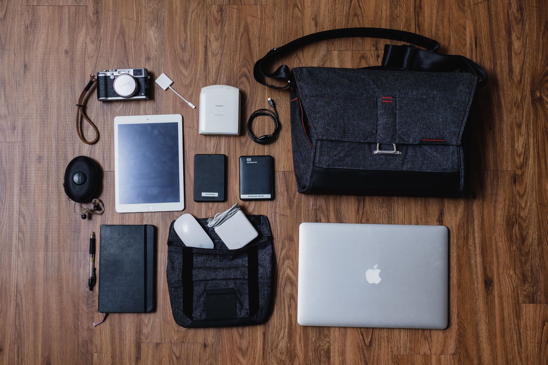 This is my other everyday setup (heavy version) 'Gotta get creative bag' -    Fujifilm X100s  camera, Apple iPad Air, Apple Lighting to SD Card Adapter,   Shure E535 Earphones,   Moleskine notebook with Pilot G-2 Pen,   Fujifilm Instax Printer SP-1,   Apple Magic Mouse, Apple MagSafe Charger, and  Apple Macbook Pro 15 ""