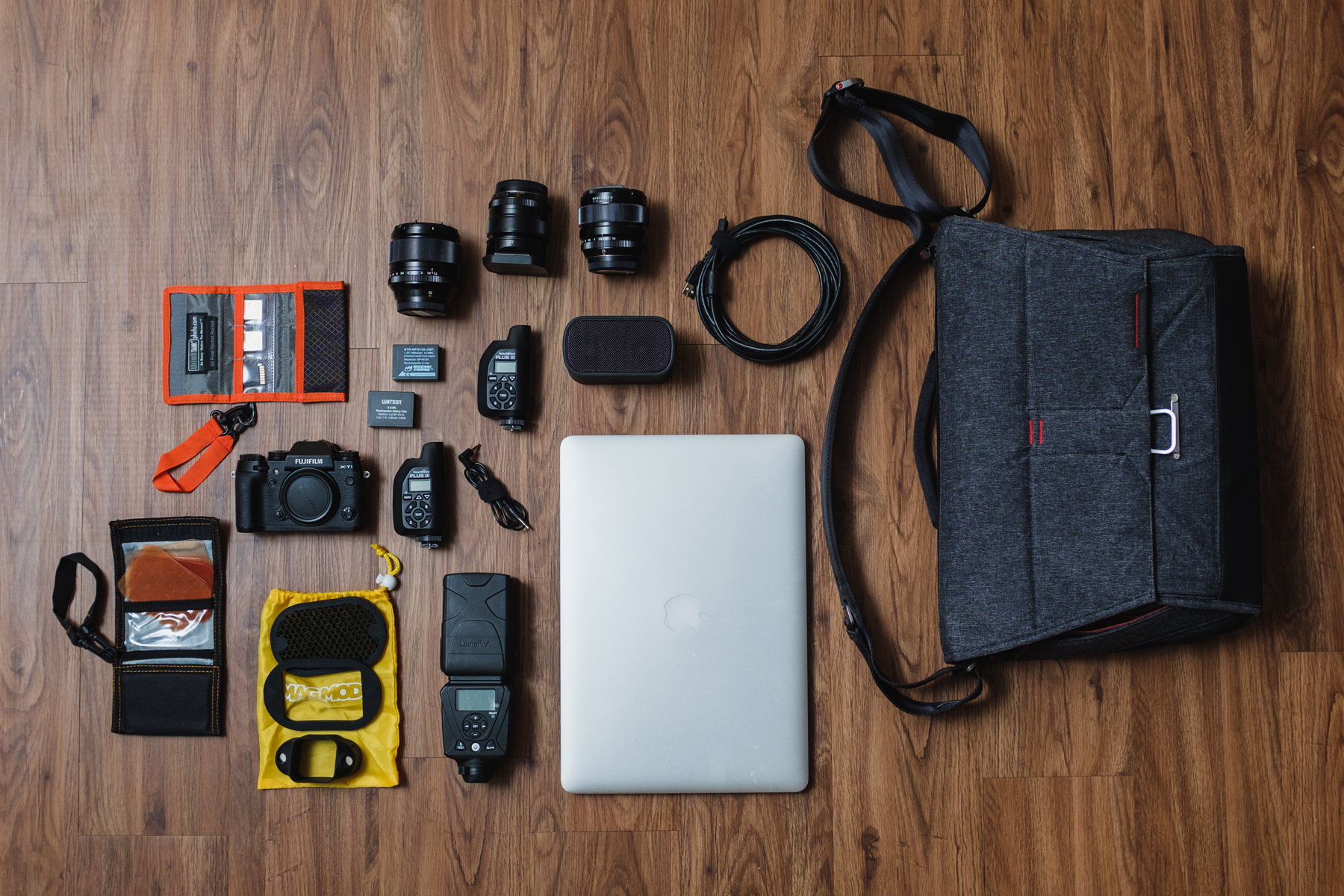 "Quick shoot setup ""I don't have an assistant and need a quick shoot bag"" - This loads up the bag very tightly.  Think Tank Photo SD Pixel Pocket Rocket  ,   SD Cards,  Fujifilm X-T1 Camera,  Fujifilm NP-W126 Batteries, Fujifilm 56mm, 35mm, & 23mm Lenses, 2x  PocketWizard Plus III Transceiver, Sync cord, MagMod Gel Kit, MagMod Basic Kit (Grid, Gel Slot, & MagGrip), Lumopro LP-180 Flash, UE Bluetooth Speaker, USB Tethering Cable, and  Apple Macbook Pro 15"""