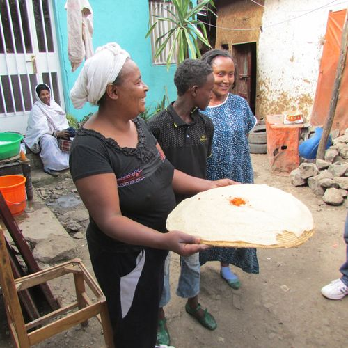 Neighbors offer the gift of Injera with ground hot pepper
