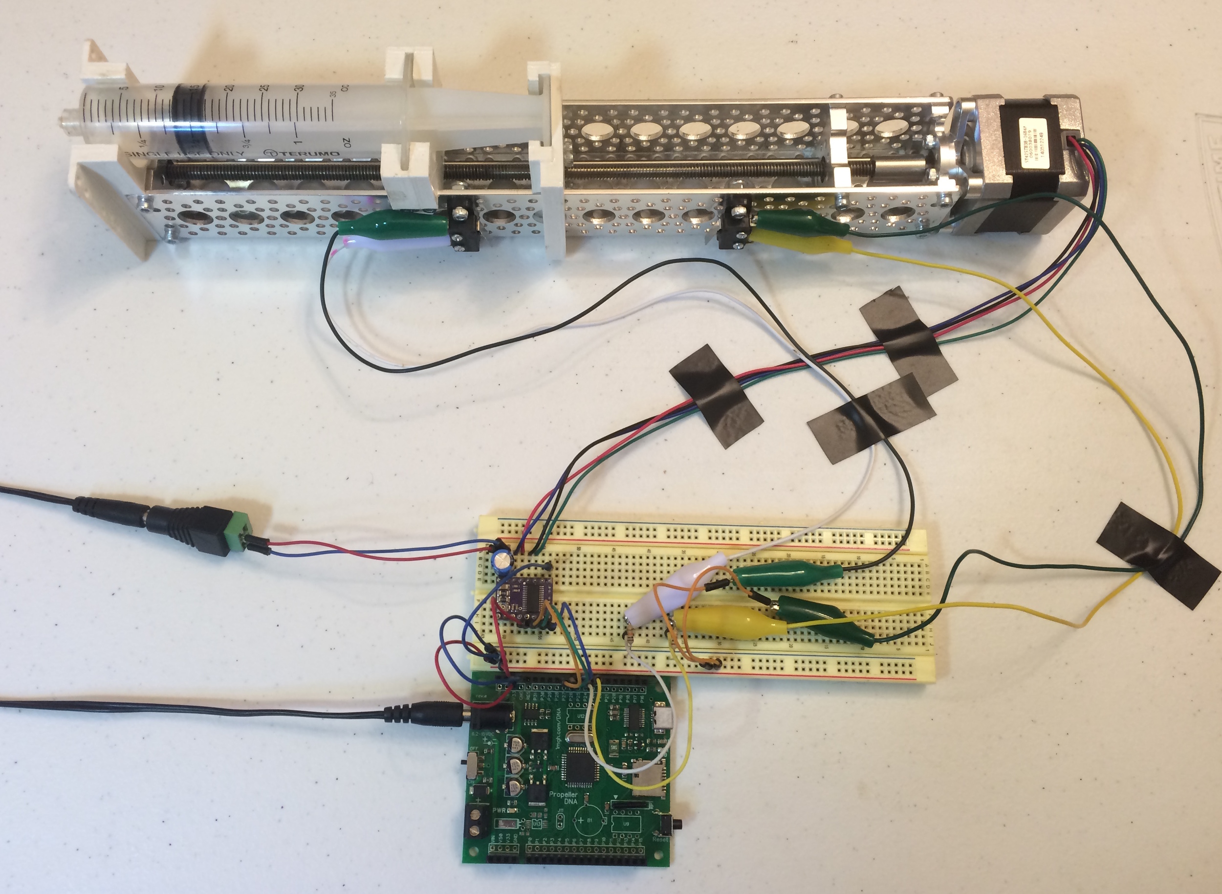 SYRINGE PUMP and completed circuit with DRV8825, PROPELLER MICROCONTROLLER, and limit micro switches. IN THIS IMAGE, THE SLEEP PIN ON THE DRV8825 IS NOW CONNECTED TO AN I/O PIN ON THE PROPELLER.