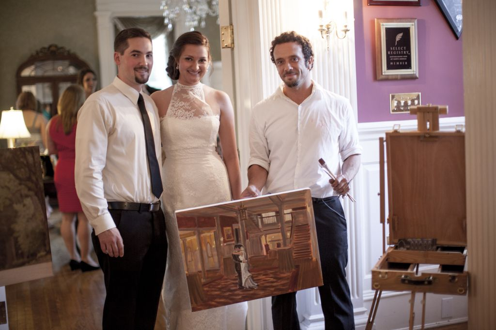 Live Wedding Painter Ben Keys of Wed on Canvas standing with bride and groom's new wedding painting.  // The Graystone Inn, Wilmington, NC // Photo Courtesy of Blueberry Creative