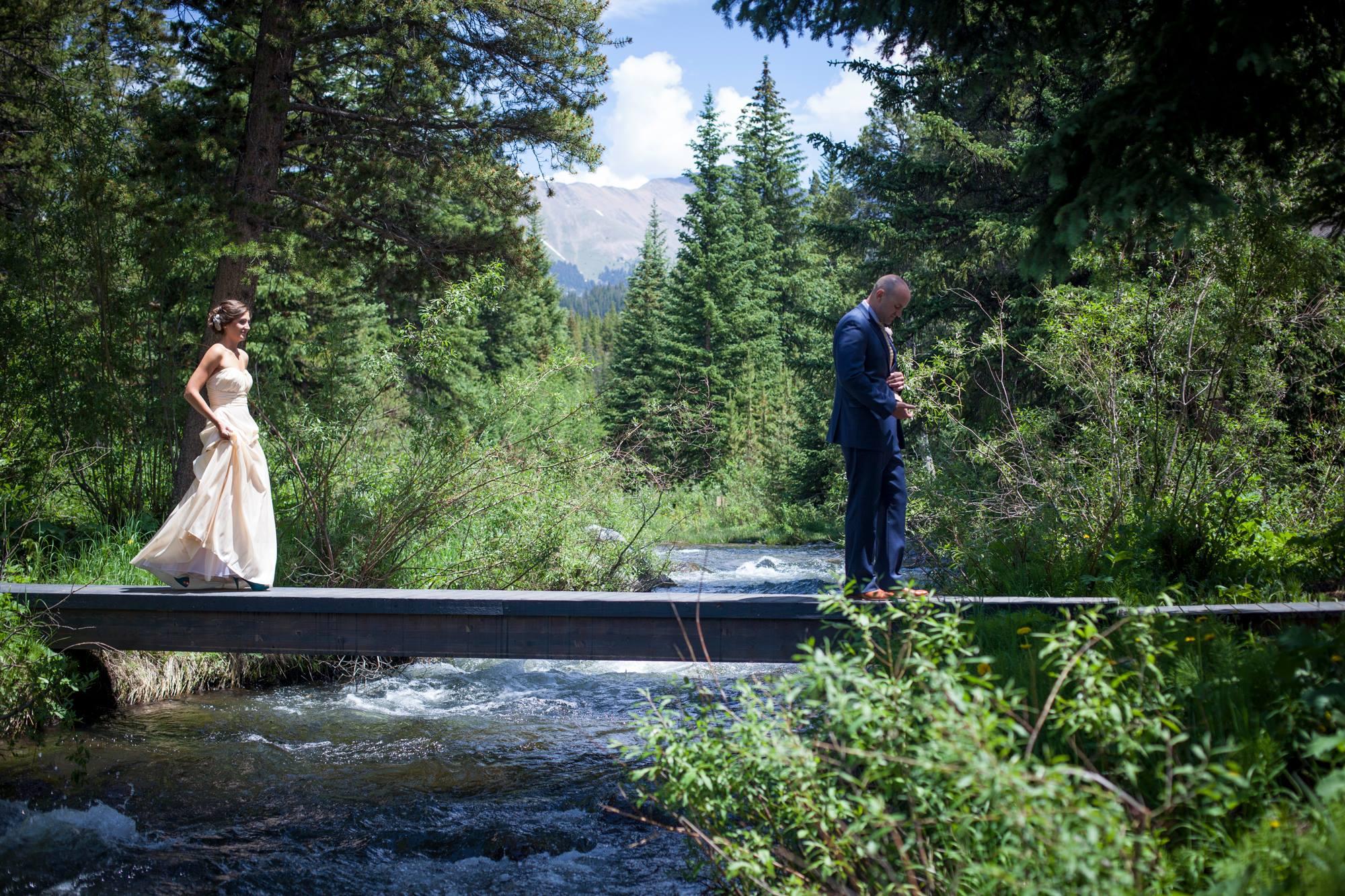 best-first-look-photo-bride-walking-across-bridge-breckenridge-colorado-wedding-painter-ben-keys-wed-on-canvas