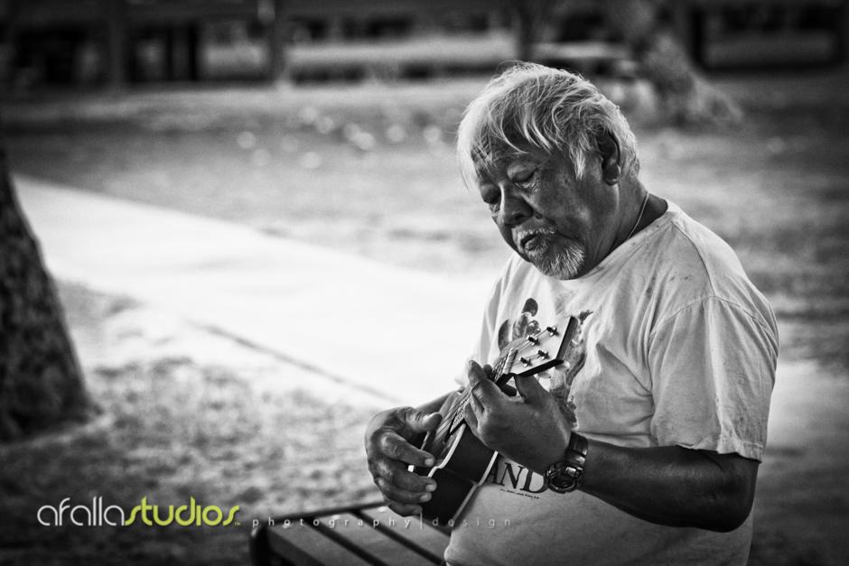 Dad playing the ukulele under the big tree.