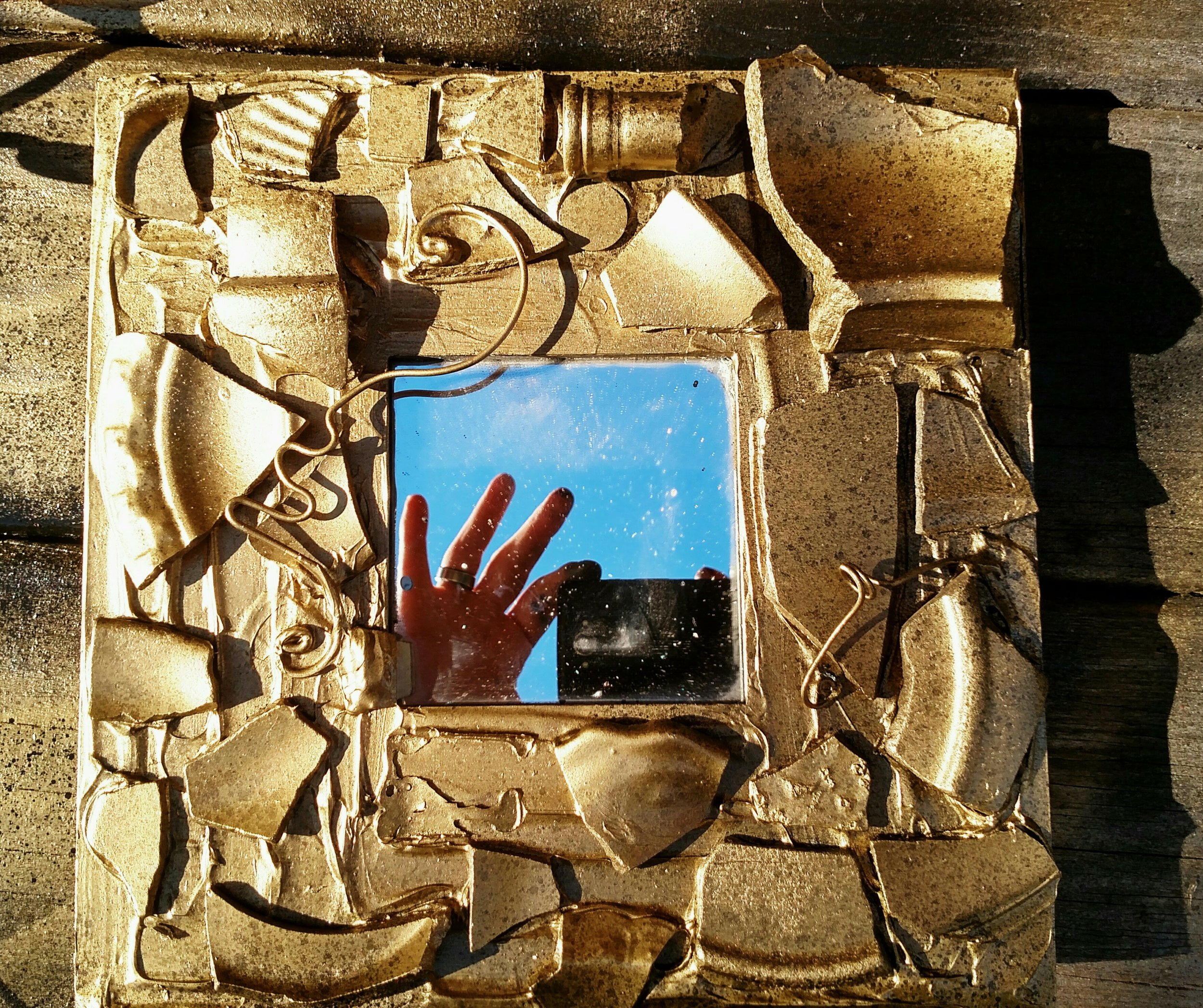 Gold frame blue sky mirror camera and fingers.jpg