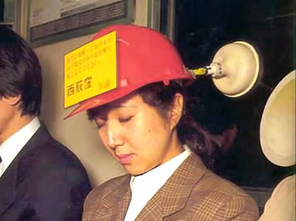 En lite knäpp uppfinning med en seriös bakgrund. Många japaner har inte tid att sova tillräckligt hemma på natten, så man tar igen det på tåget eller kanske på ett fik mellan två möten på stan. Skylten på damens hjälm berättar om inför vilken station hon skulle vilja väckas. Sugkoppen förhindrar att hon sover mot någons axel.