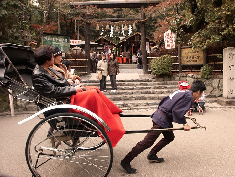 """Turister åker rickshaw i Kyoto. Rickshaw är en förkortning och anglifiering av japanskans  jinrikisha  (人力車), ordagrant """"människokraftvagn"""".  Foto: Public Domain"""