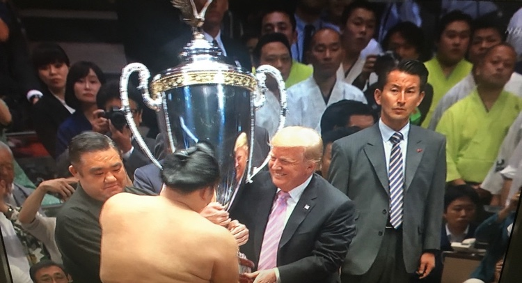 """— och Trump överräckte sin """"presidential trophy"""" med viss hjälp av japansk assistans till vänster.."""