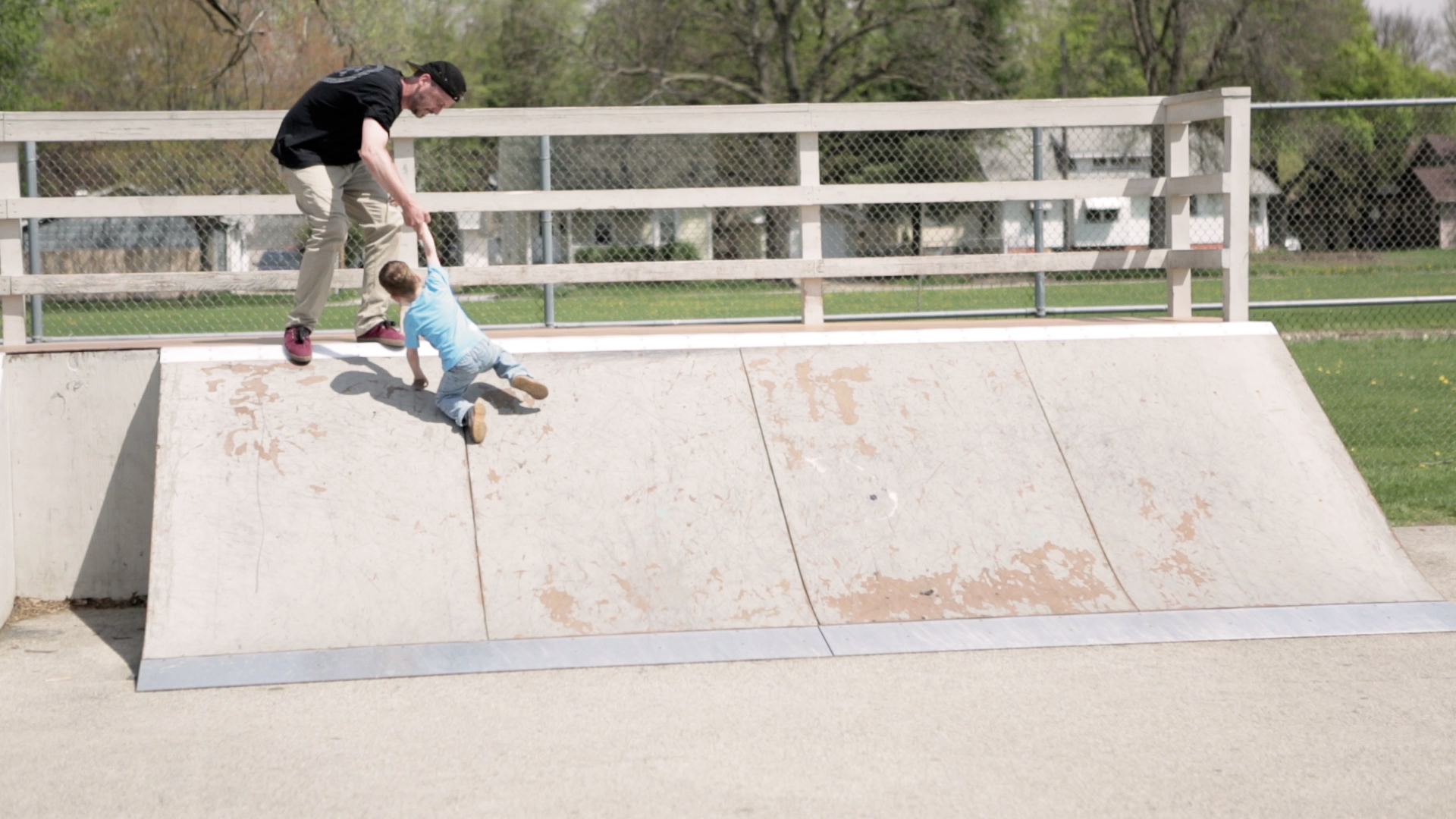 Eric helps Johnny, his second son, crest the ramp at Churchill Park, a neighborhood skatepark he lobbied to get built.
