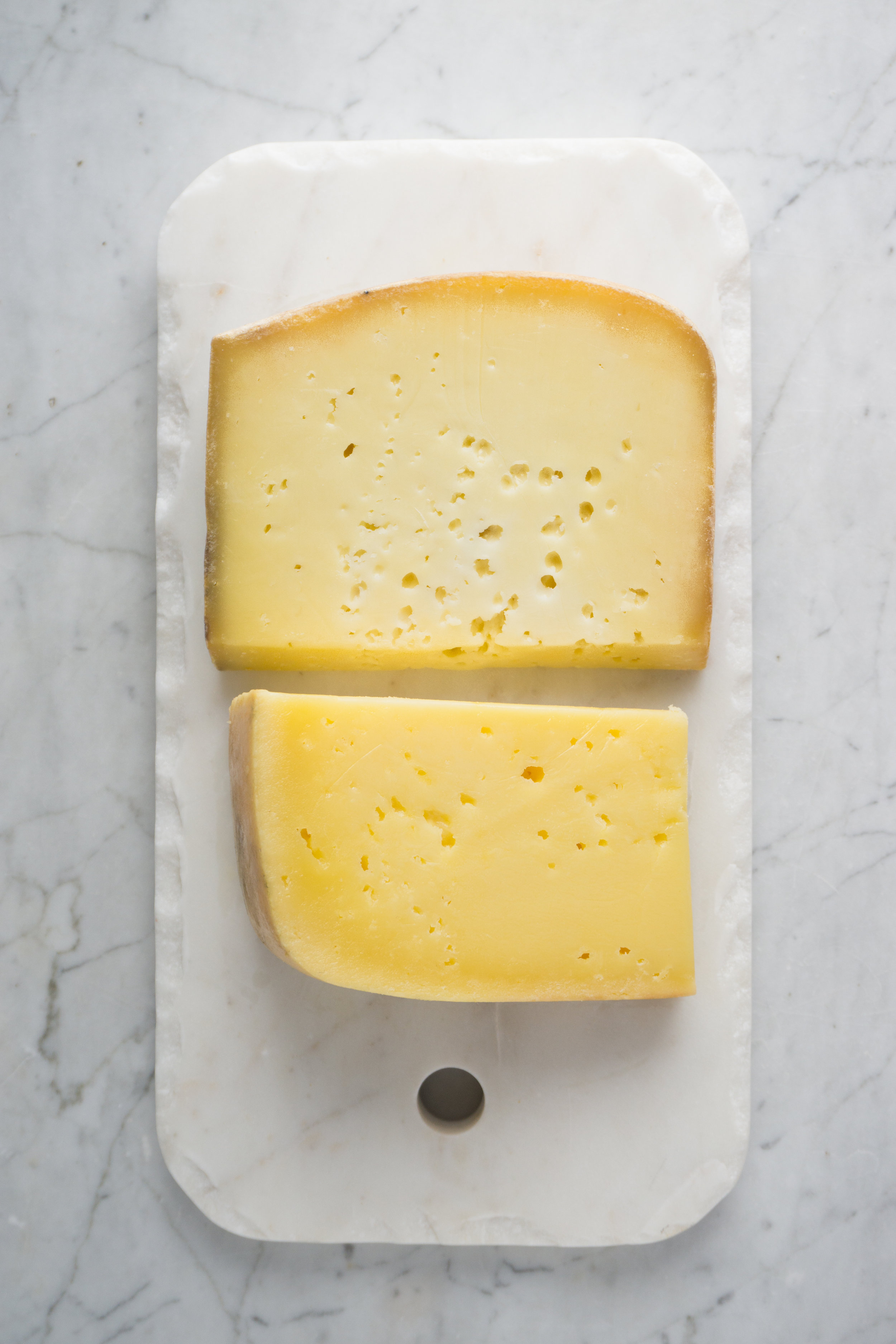 Seasonal changes, what cows eat and pasteurization create subtle changes in milk and therefore the color of cheese. Above:  Appleton Farms Pinnacle  (winter, pasteurized milk, lighter color), below:  Robinson Farm's Robinson Family Swiss  (summer, raw-milk, more yellow/orange from the pigments in the fresh grasses).