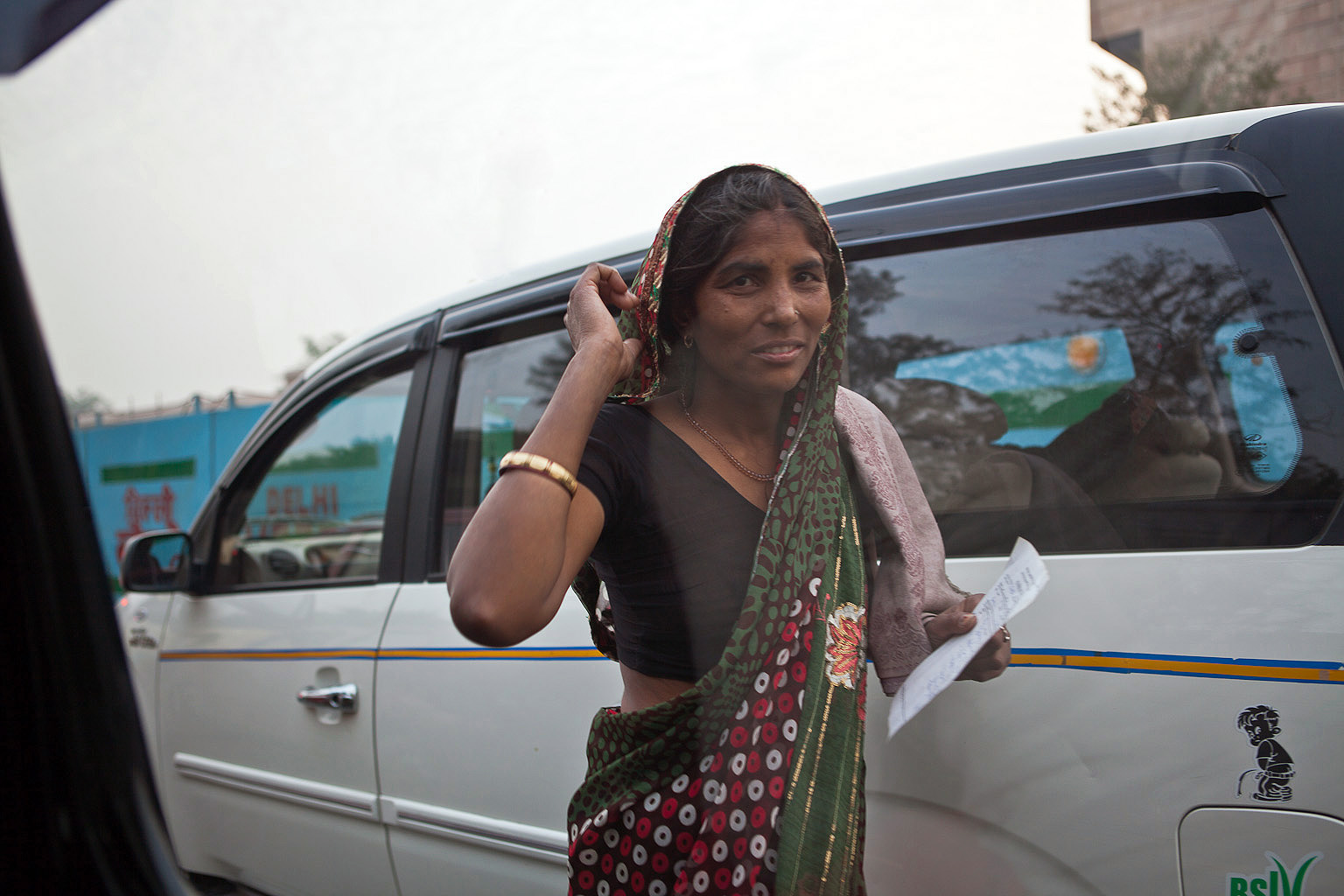One of my all time favourites. This lady was trying to sell something to the commuters on their way home. I was about to put my camera away but shot through the glass at the last minute.