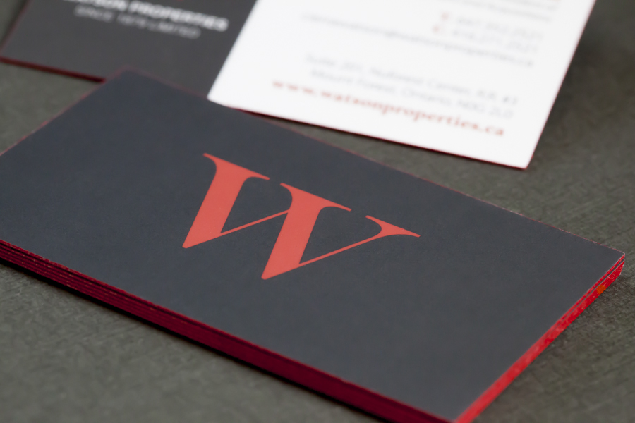 Soft-touch business cards with red painted edges.