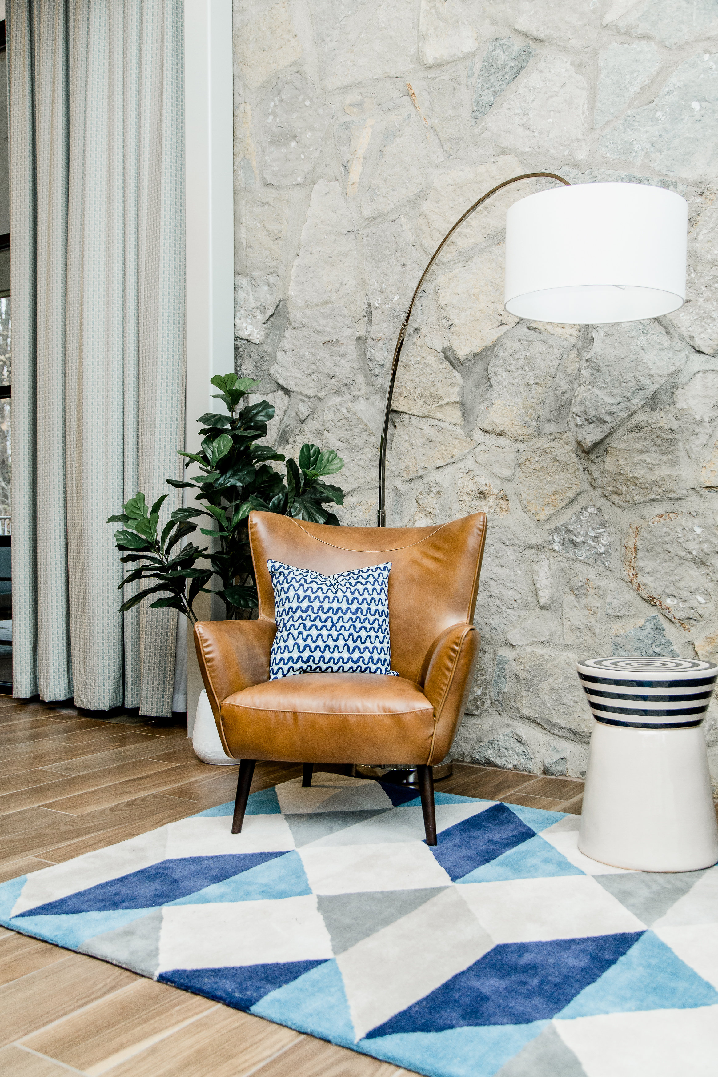 A note from the designer: Midcentury design can look too linear and stark, if you're not careful. So we used plants to warm up the space, a little. We were lucky that the client wanted to keep the original stone walls in the living room space, as well. That was a beautiful texture to play off of. We placed two beautiful leather chairs in front of the wall, in addition to a fiddle leaf fig plant. The chairs are a beautiful, supple leather which is in direct contrast with the rough, stone wall. And of course the fiddle leaf adds visual interest and dynamic movement.