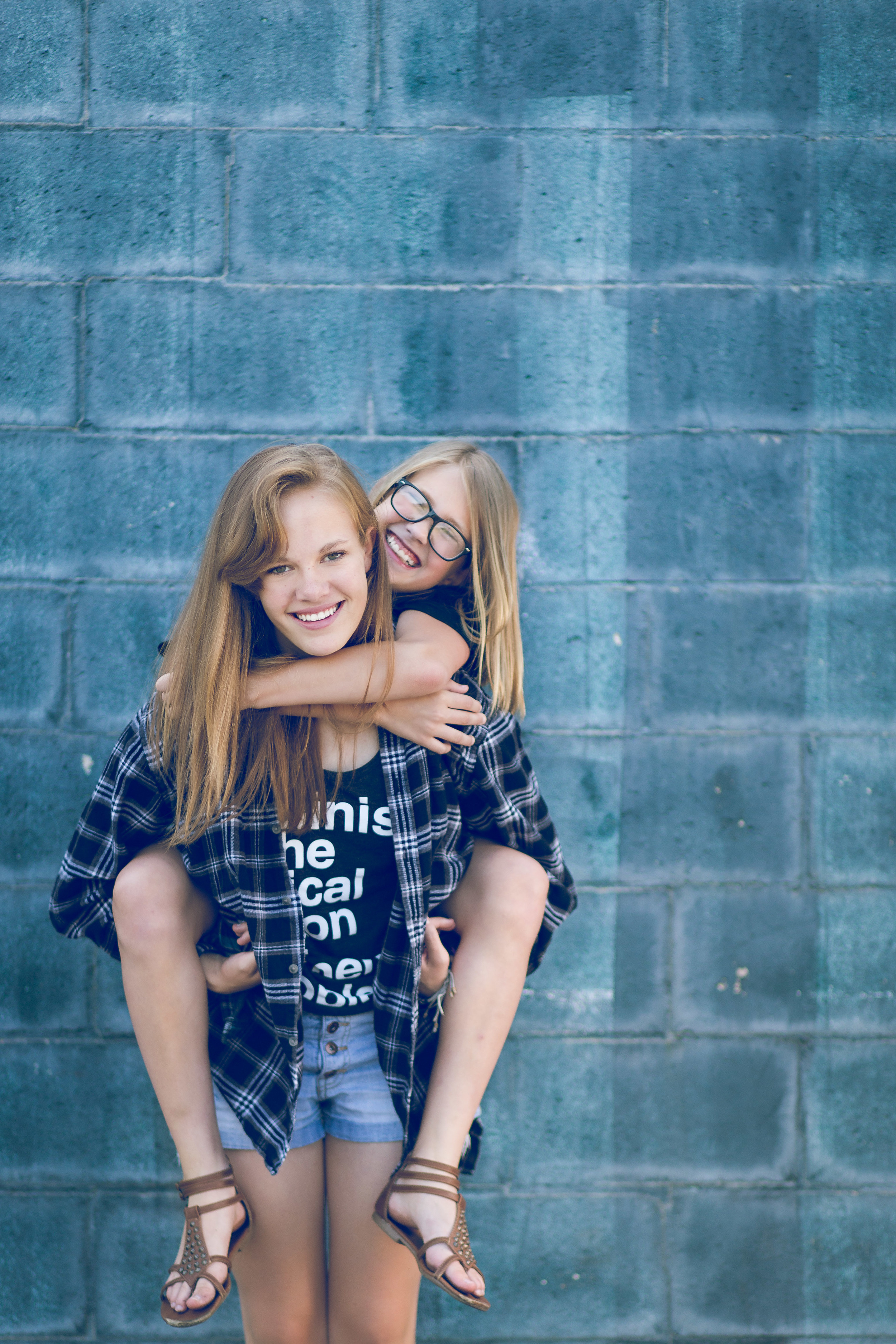 tween portrait of two girls ain front of blue wall