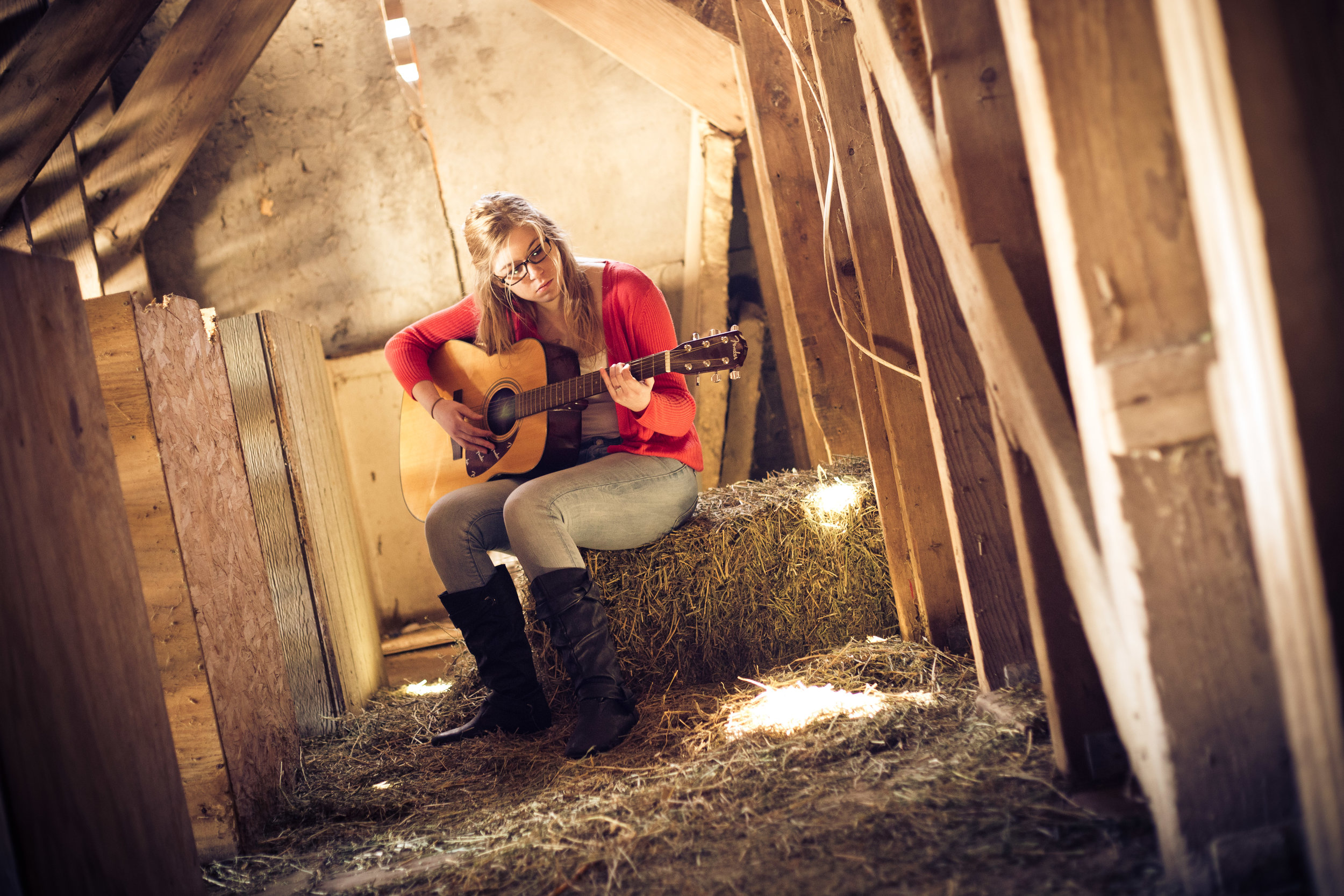 senior portrait of a girl playing guitar in barn
