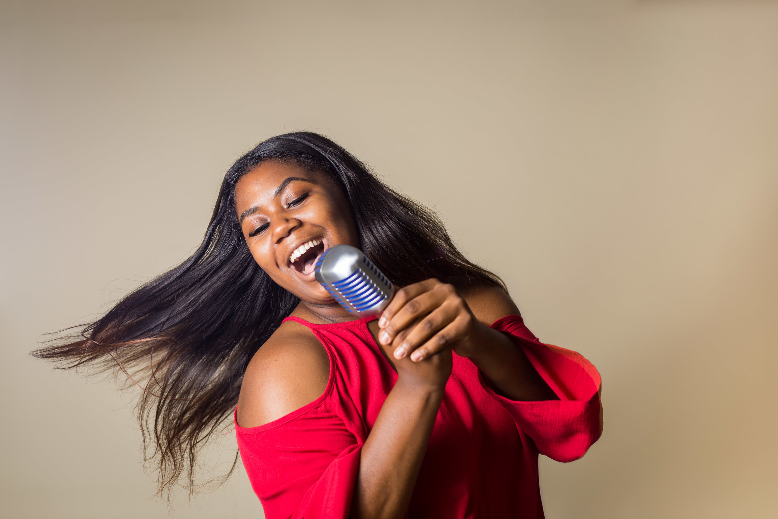 senior portrait of a girl singing into a microphone