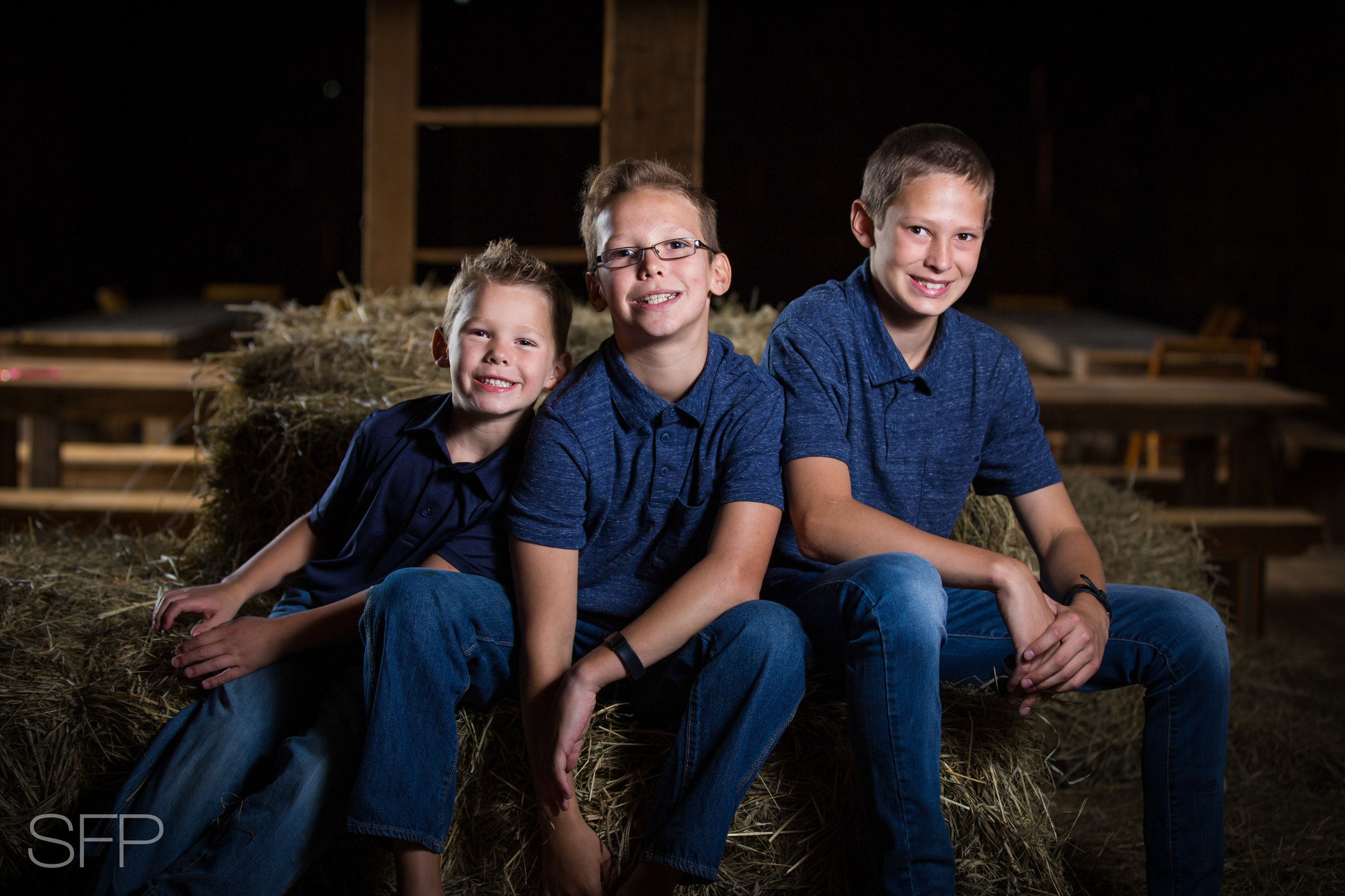 brothers sitting on hay in a barn
