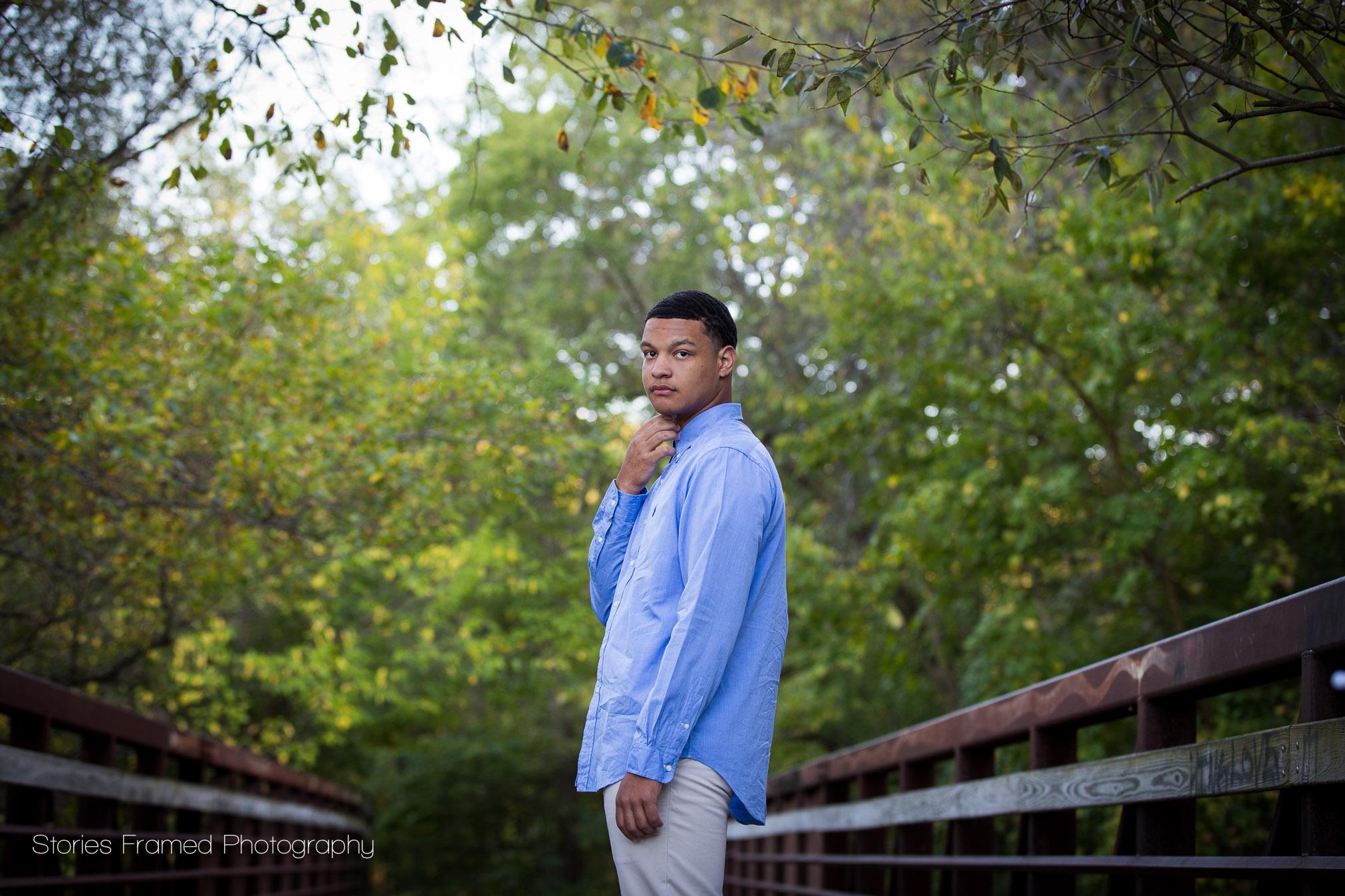 senior boy in a blue shirt on bridge