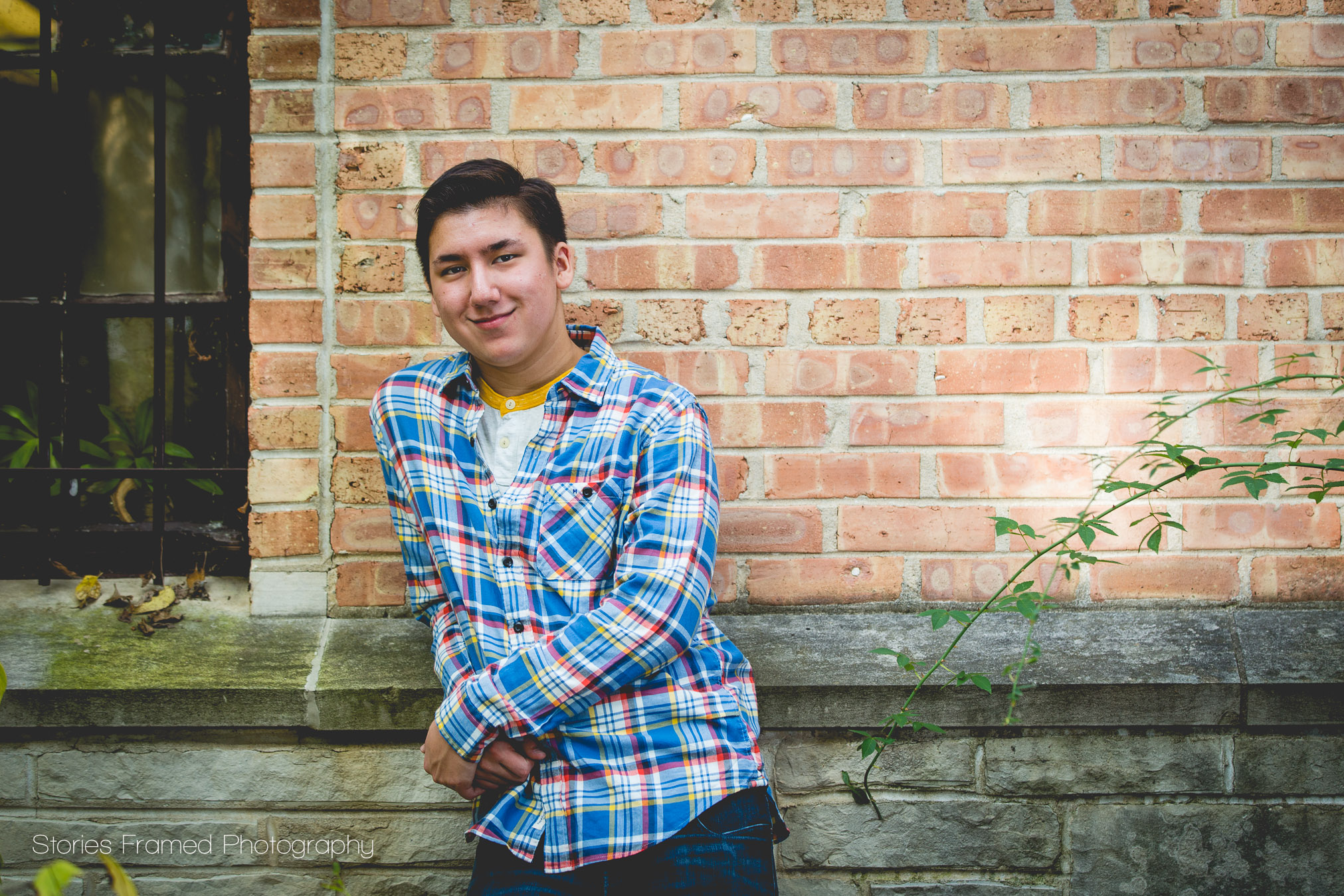 senior boy in plaid shirt leaning on brick building