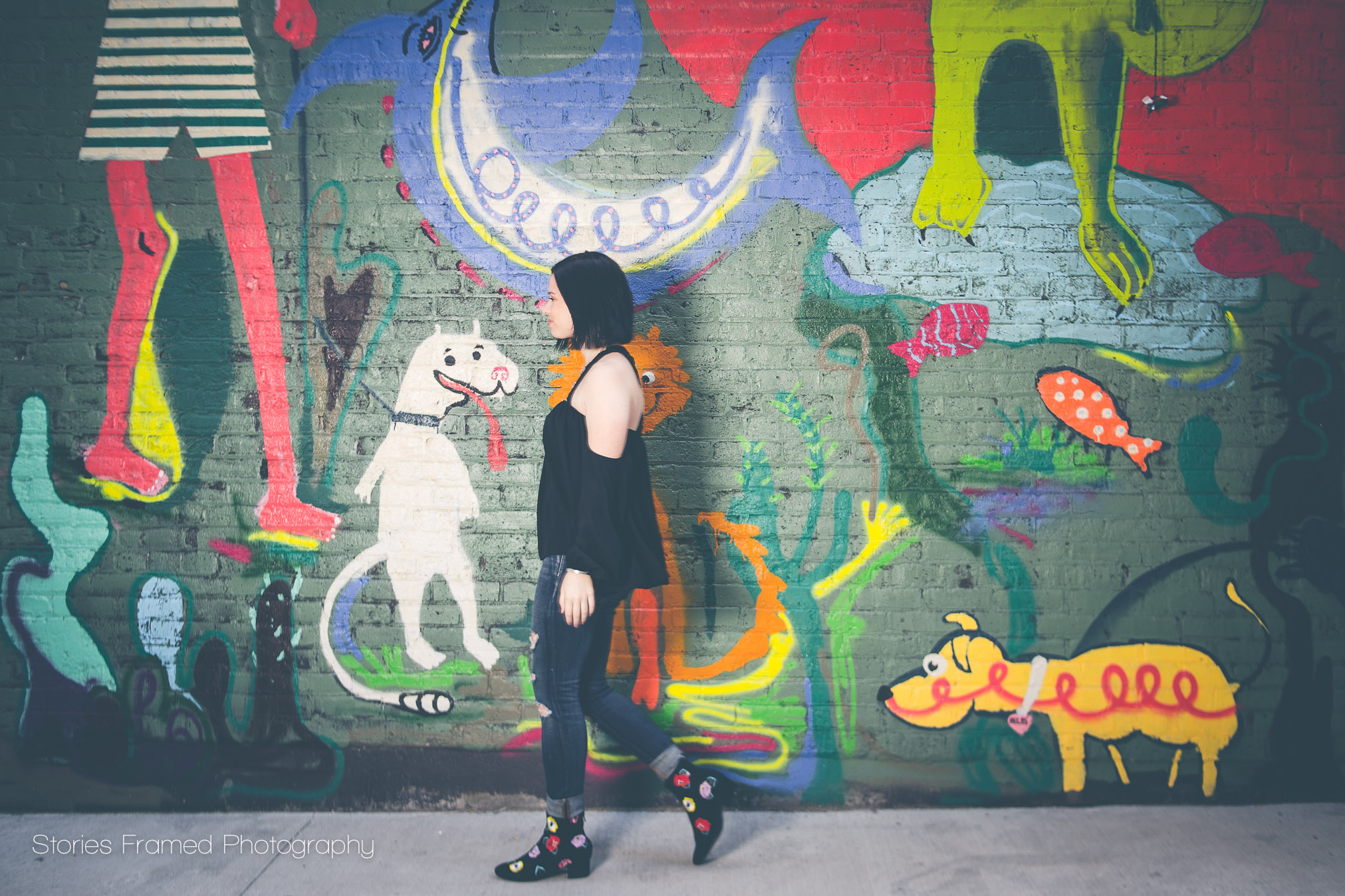 girl walking by painted mural