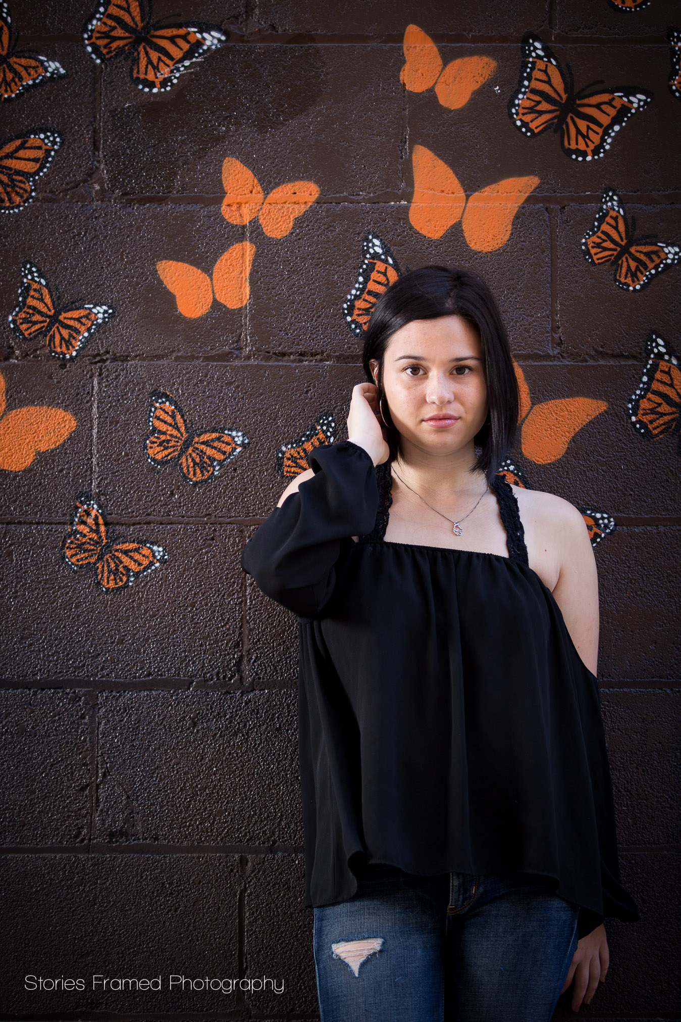 girl in front of butterfly wall
