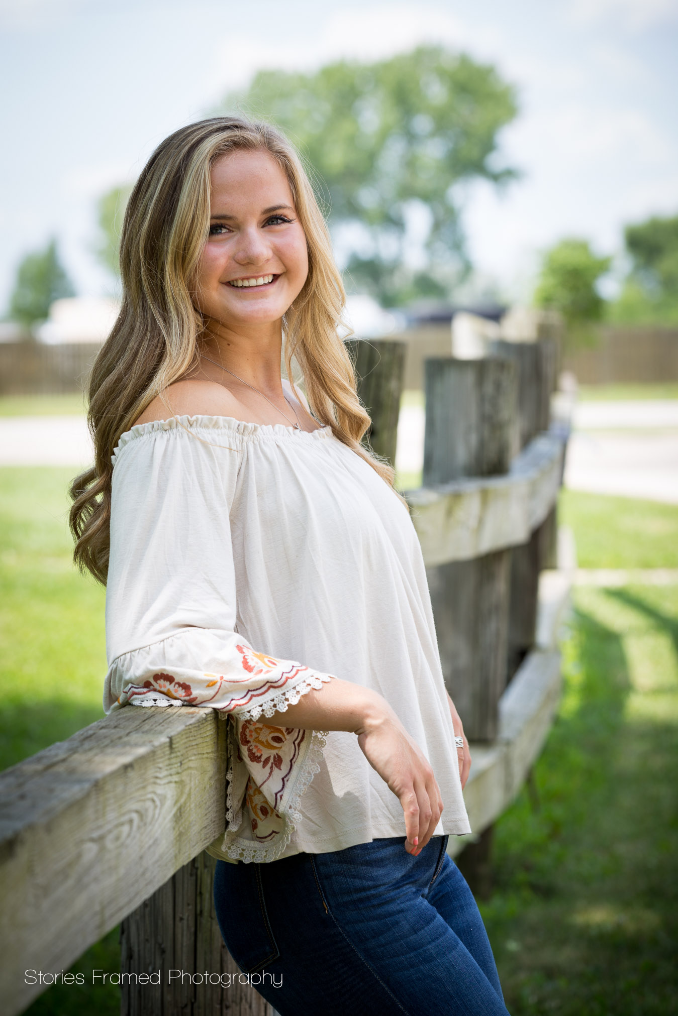senior girl leaning on wood fence