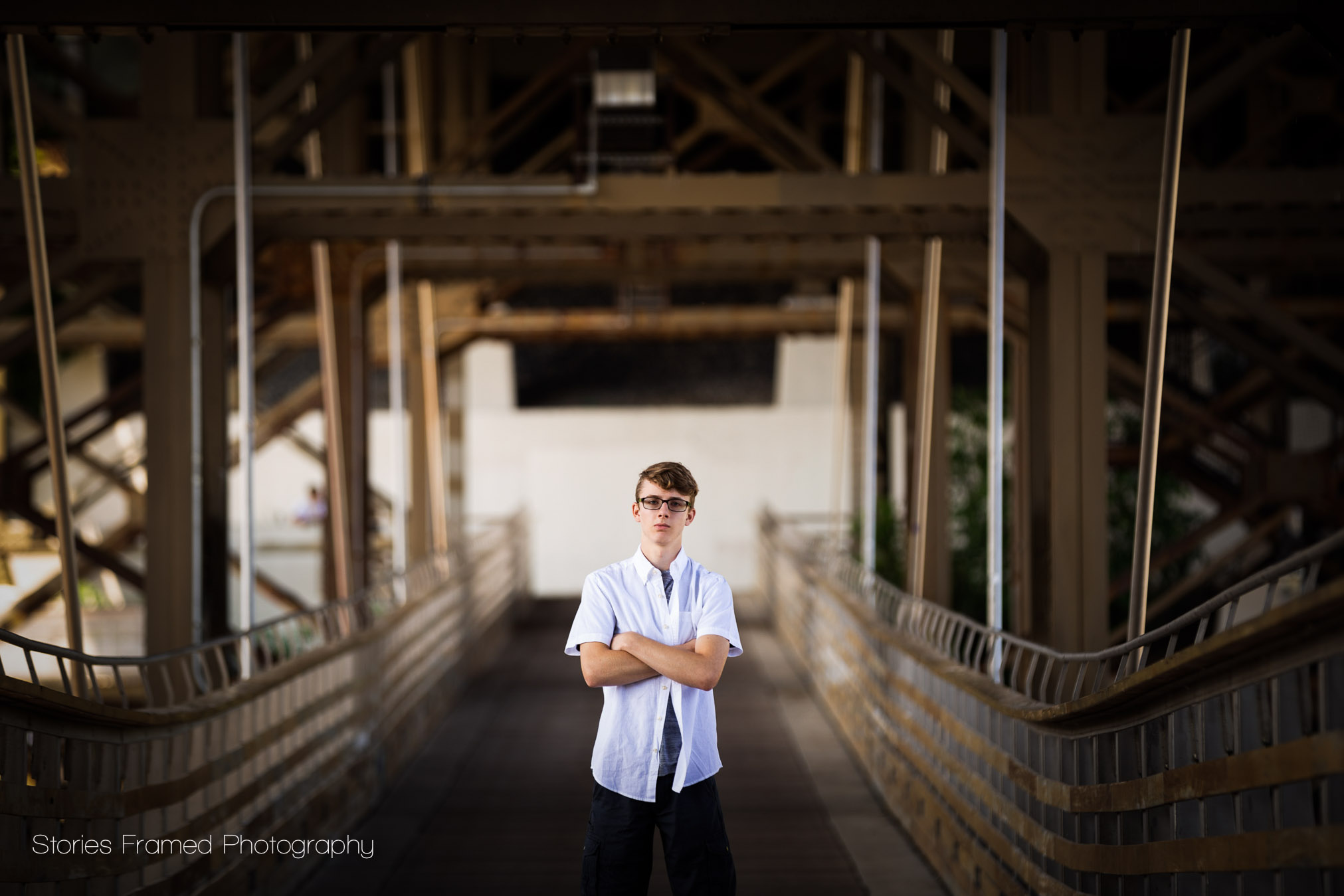 senior posing on a bridge