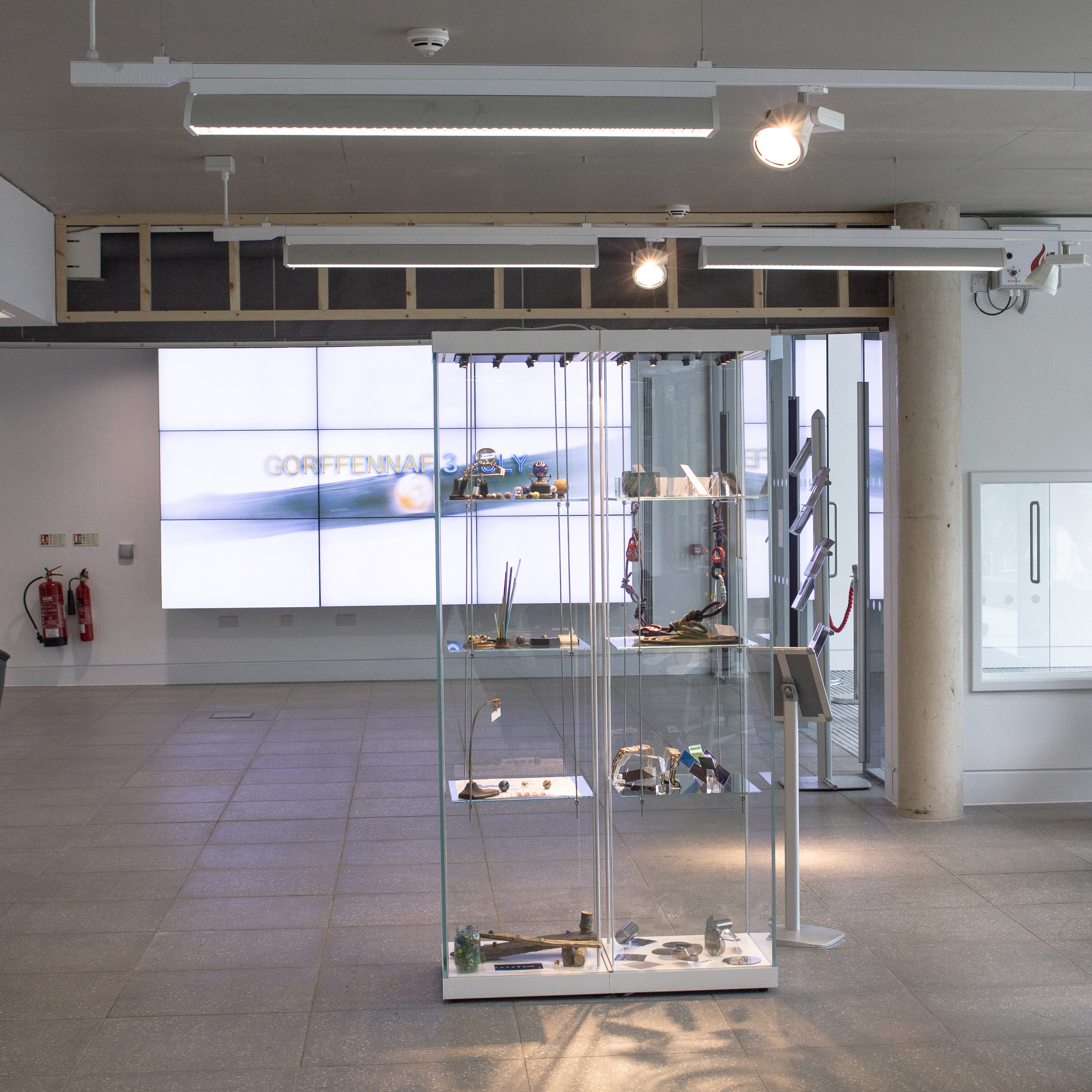 Llif/Flow display cabinet in the foyer at Pontio: The left hand side of the cabinet in the picture below, with the Vertical Light and Dance experience Synthesis project (running concurrently) in the right hand side... and our promo film in the background.
