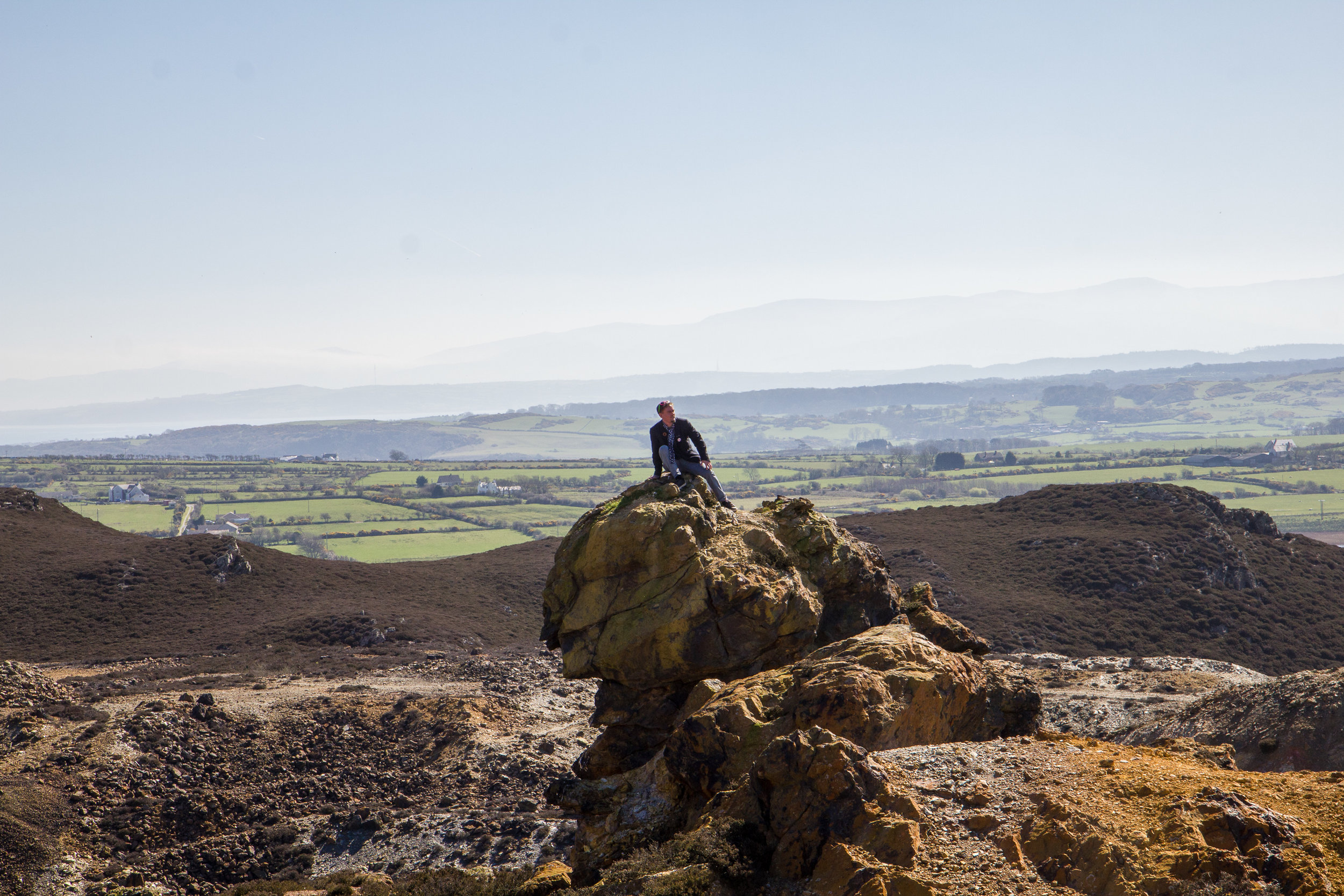 Bard (Rhys Trimble) ar y top. Mountains of Snowdonia behind, across Anglesey plain and the Menai Straights