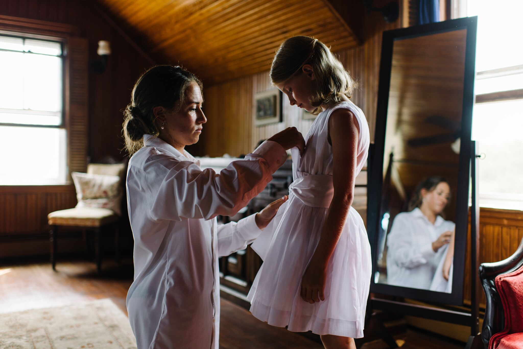 Bride helping dress flower girl at a wedding