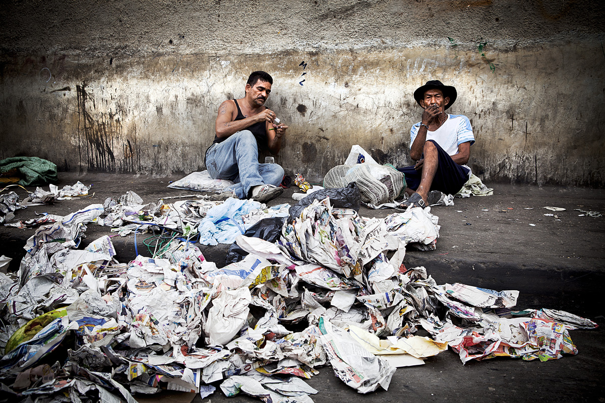 Man on the left refills crack pipe while man on right smokes a cigerette as they wait for recyclables to arrive.  Barranquilla, Colombia 2014.