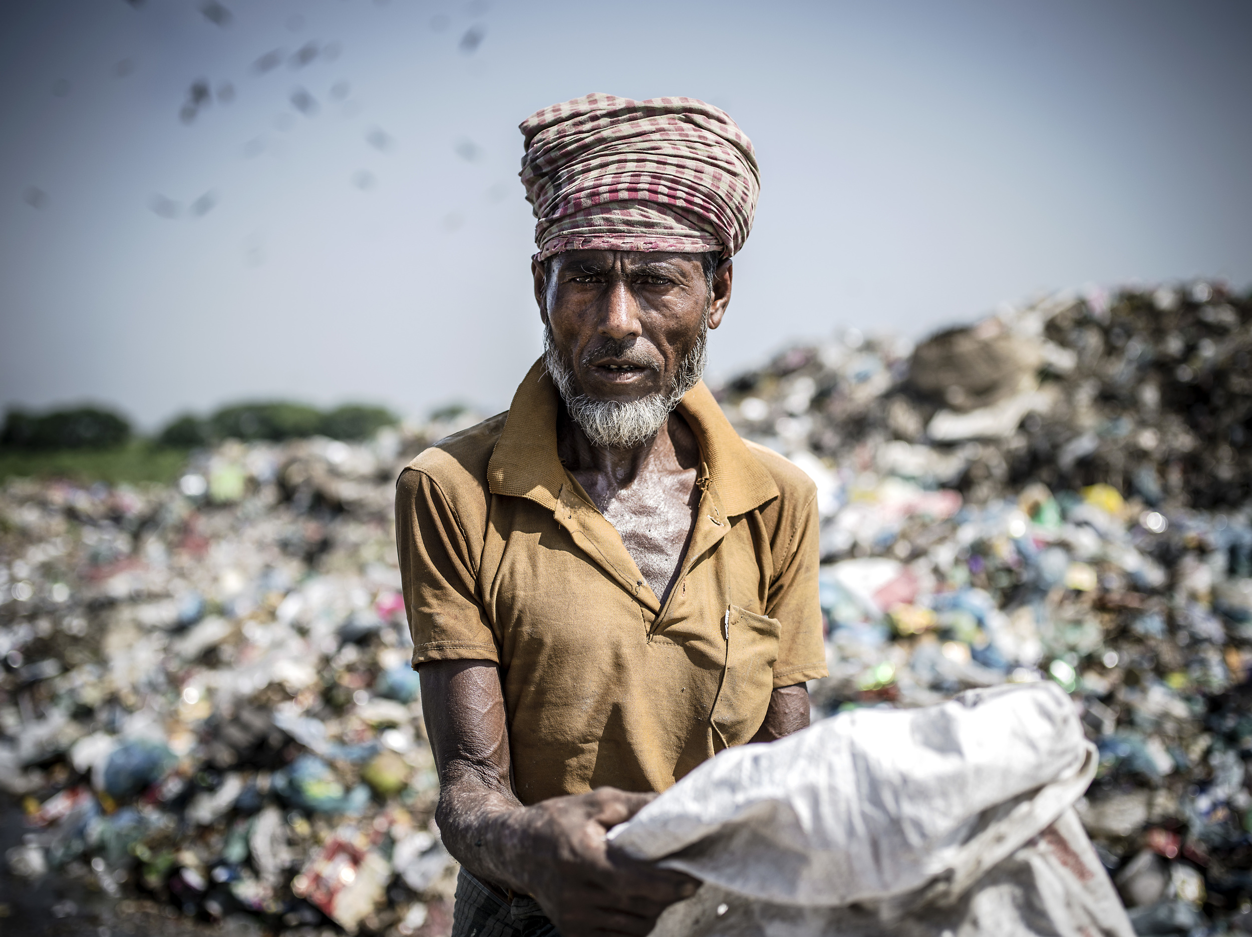 A man  informally recycling  at Parar Chokh Landfill in Sylet, Bangladesh.
